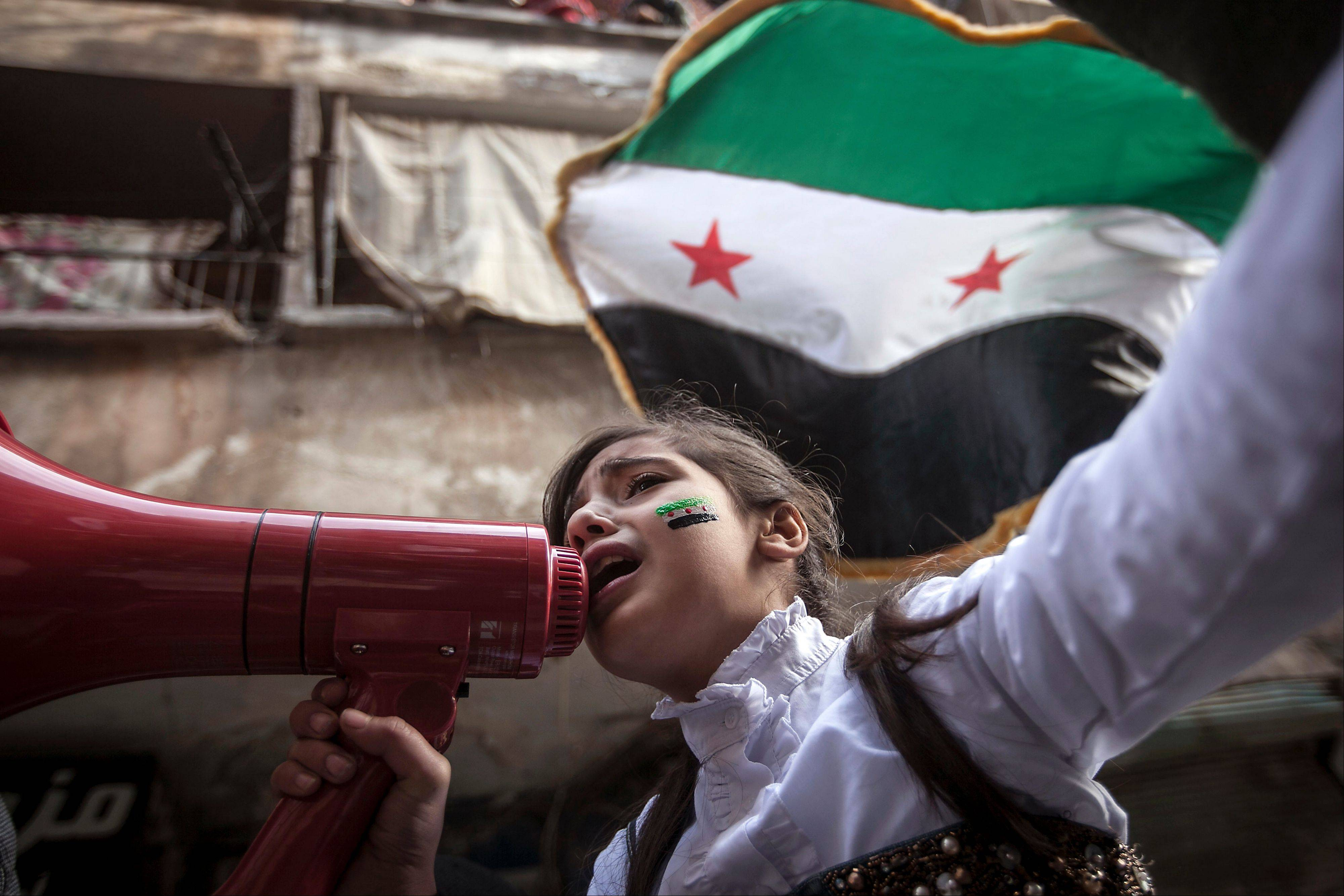 A Syrian girl chants slogans Friday during a demonstration in the Bustan Al-Qasr district of Aleppo, Syria. After months of fighting, thousands of residents have returned to the city as they attempt to return to their daily lives.