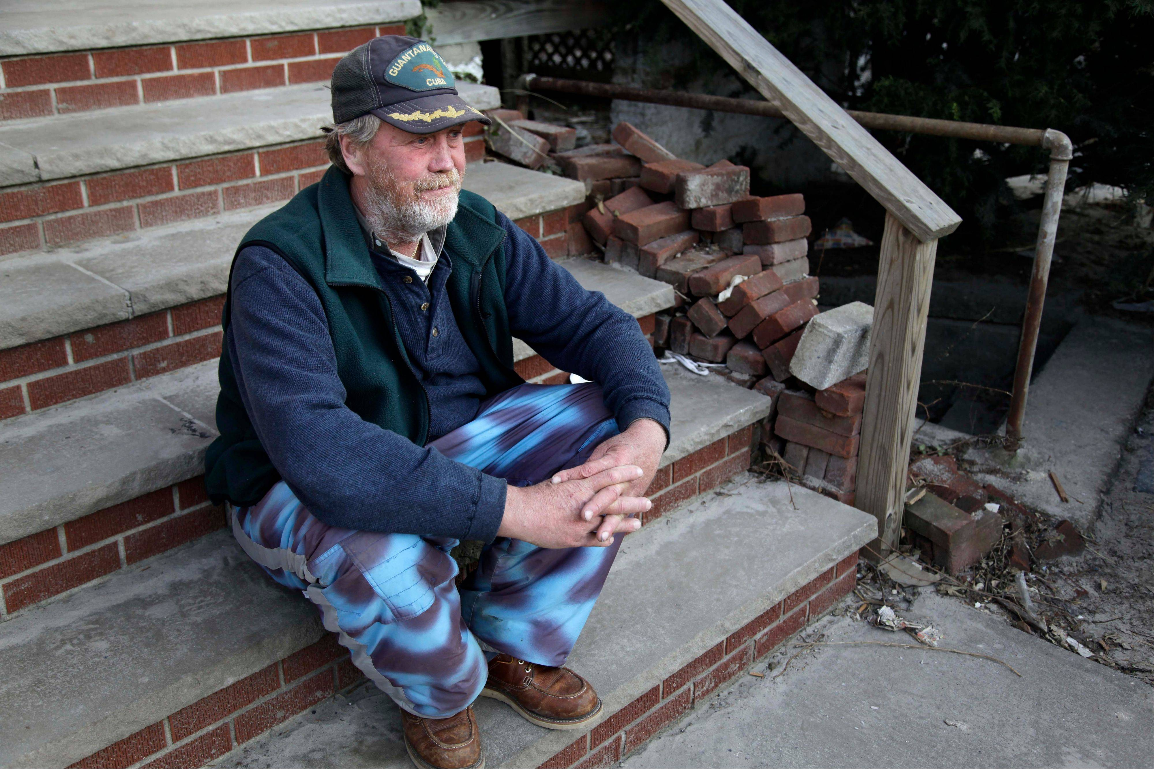 John Frawley sits on the porch of his house, which was damaged during Superstorm Sandy.