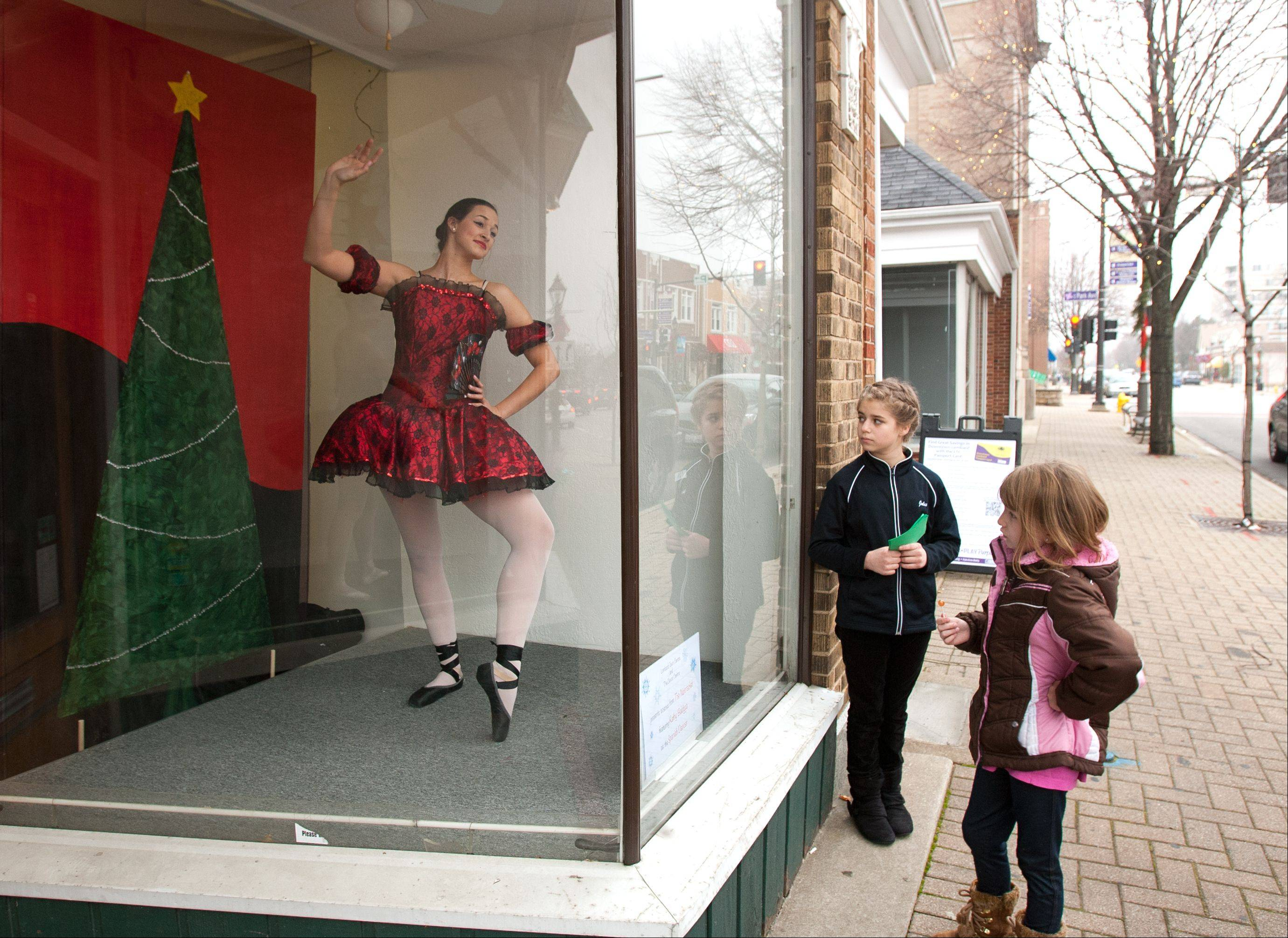 "Kathy Baldyga plays a Spanish Dancer, as she, along with other dancers perform scenes in storefront windows from ""The Nutcracker"" during the Jinglebell Jubilee in Lombard. Julia Walli, 11, center, and Lauren Wilinski, 7, both of Lombard, watch from the sidewalk."