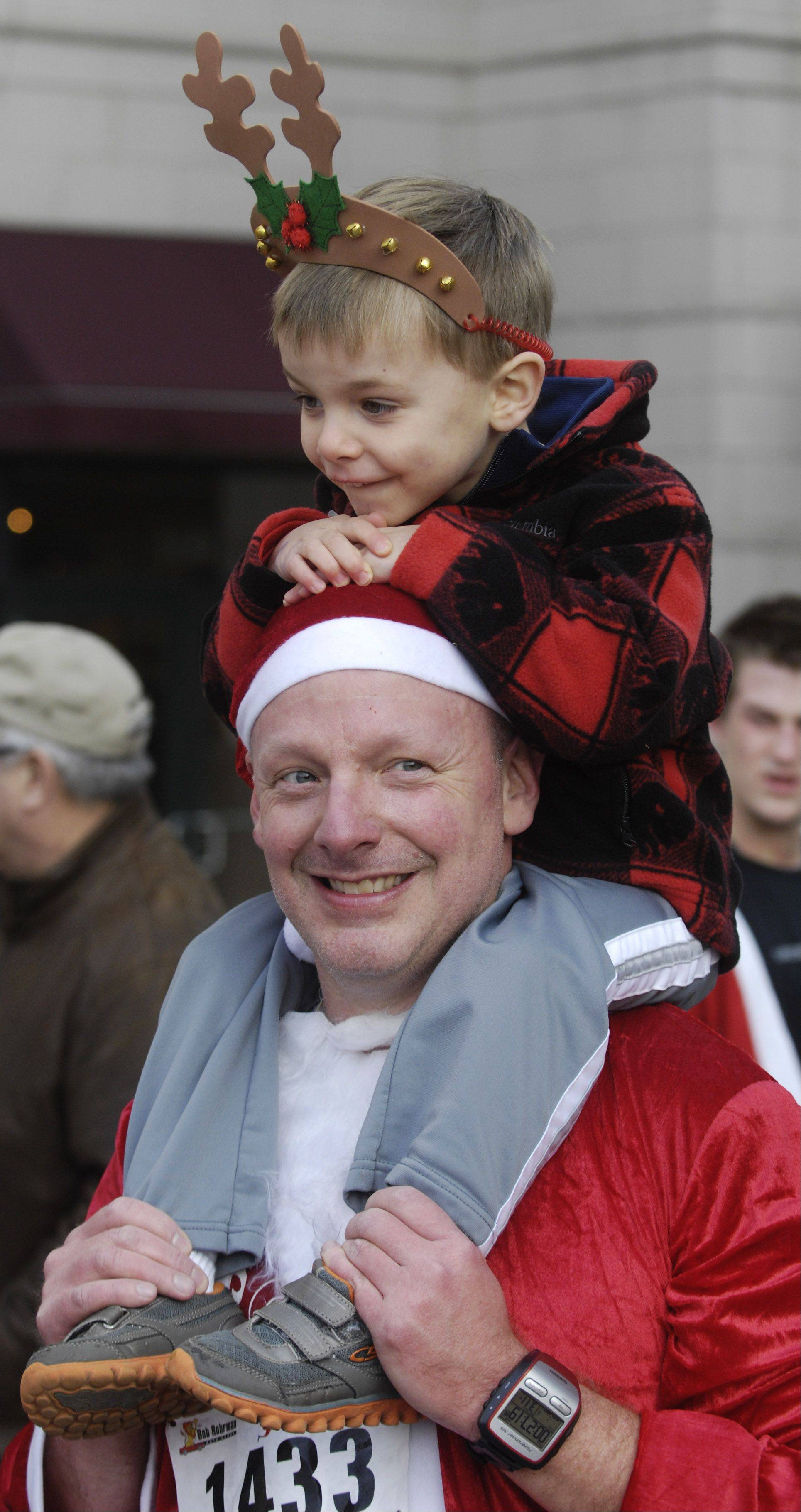 Tommy Wagner, 3, of Mount Prospect is seated on the shoulders of his dad, Ken, following Saturday's 5k Santa Run in Arlington Heights. Tommy turns four on Christmas Day.