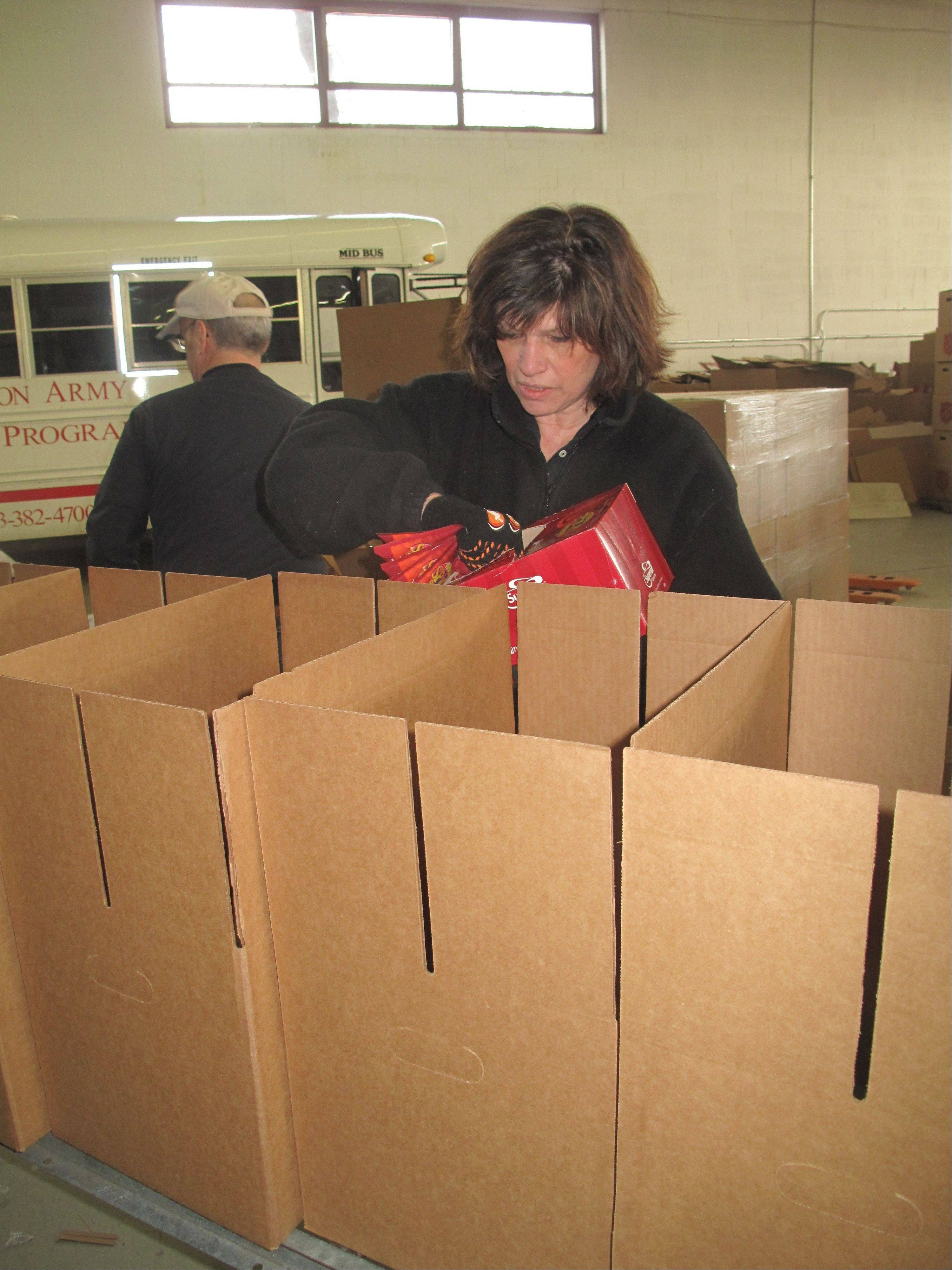 Ruthann Botica of Chicago adds pumpkin spice cappuccino packets to an assembly line of Christmas food boxes being packaged Saturday at the Salvation Army Metropolitan Division's Disaster Services Center in Elk Grove Village.