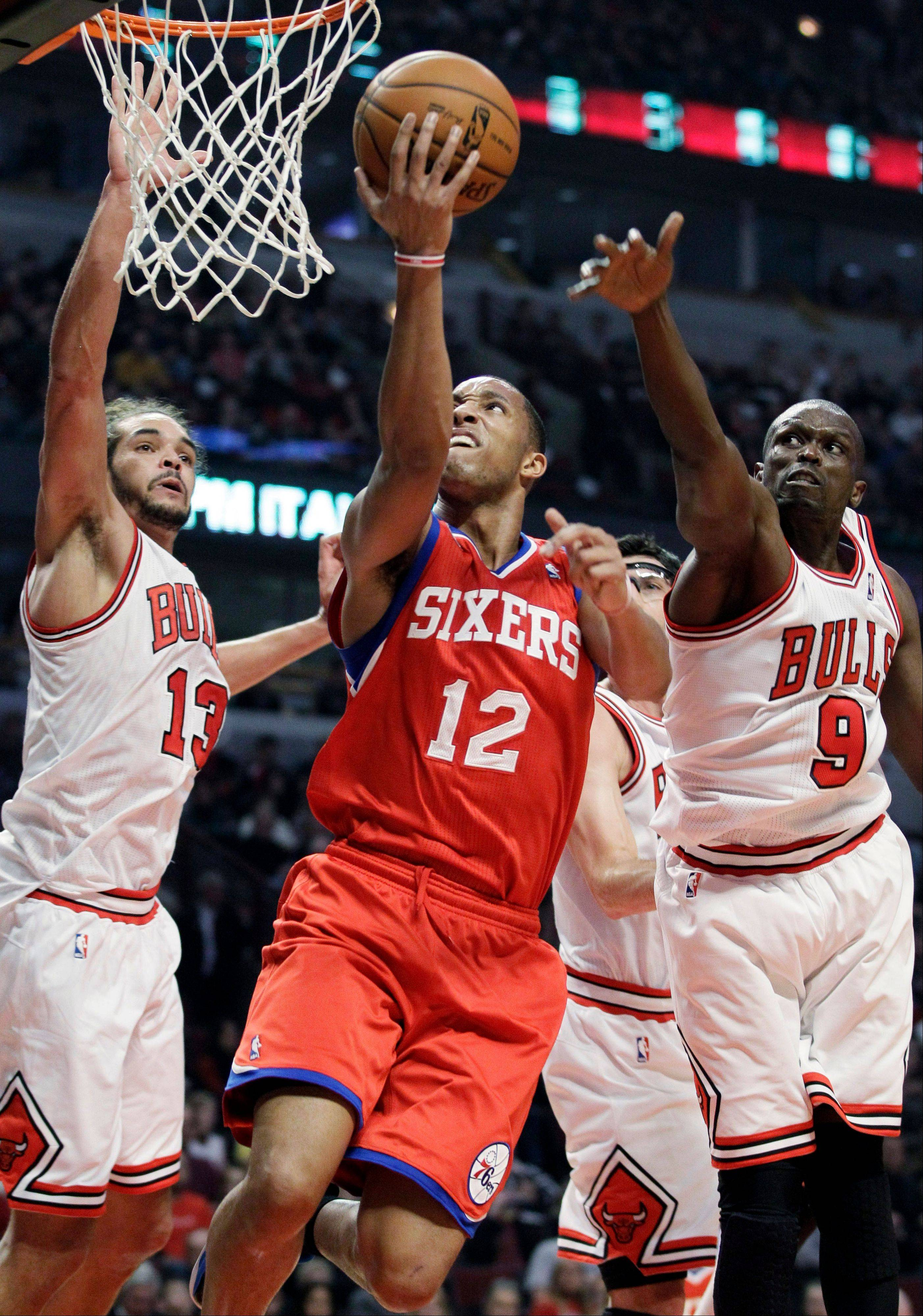 Philadelphia 76ers forward Evan Turner, center, shoots against Bulls center Joakim Noah (13) and forward Luol Deng during the first half of an NBA basketball game in Chicago on Saturday, Dec. 1, 2012.