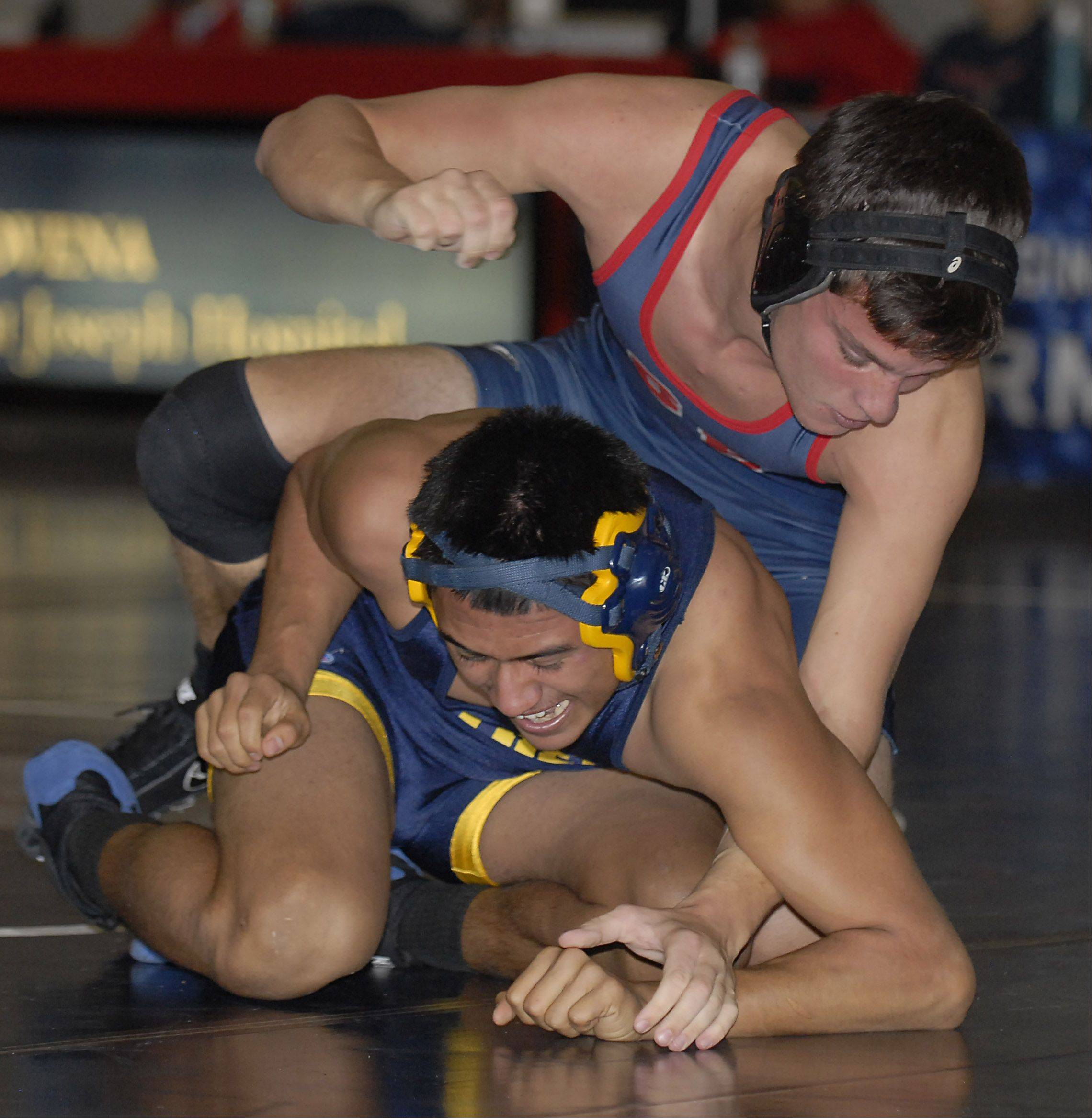 South Elgin's AJ Venturella reaches to wrap his hands around the wrists of Round Lake's Juan Mena in the 152-pound match on Saturday, December 1.