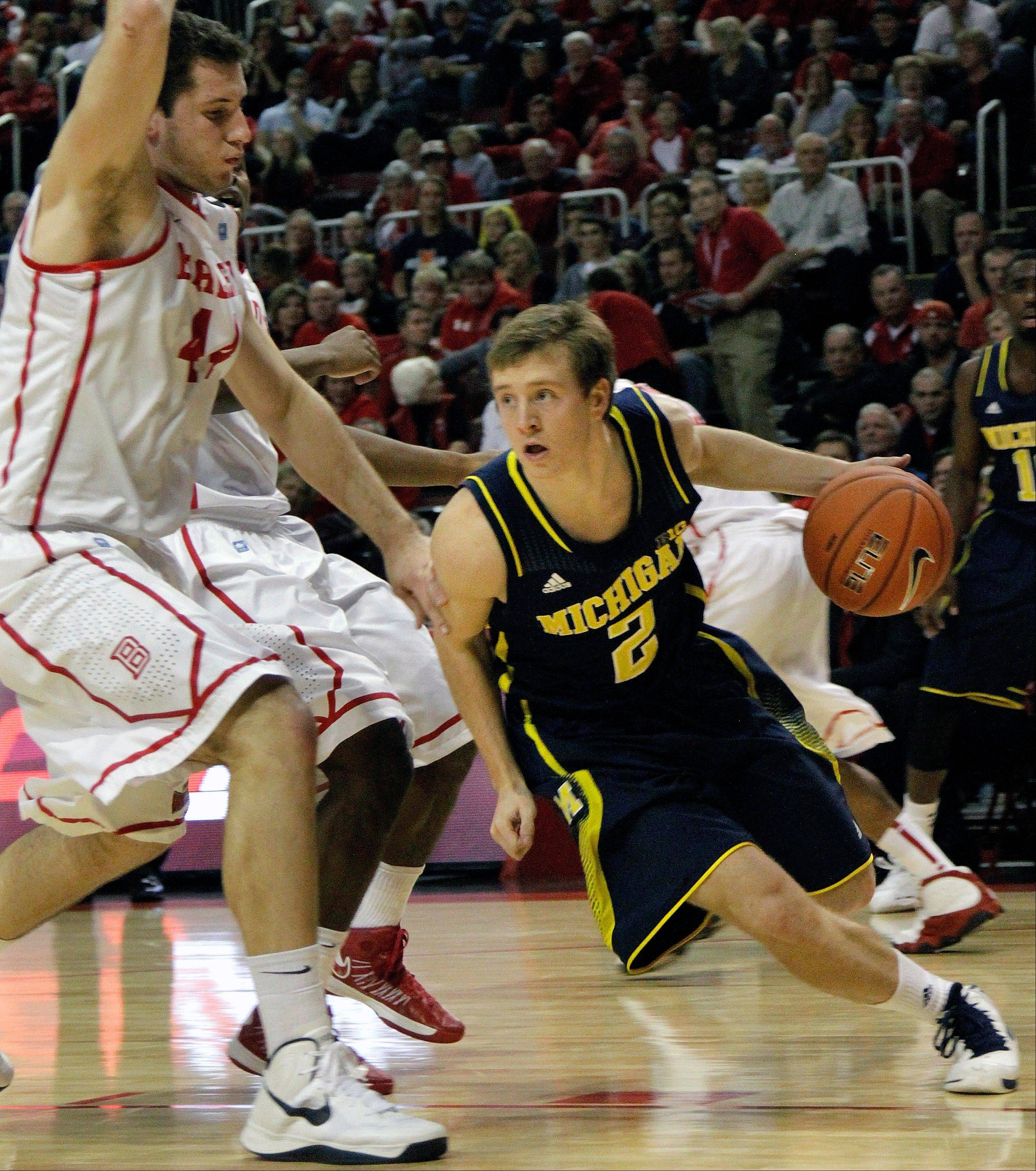 Michigan guard Spike Albrecht goes against Bradley center Jordan Prosser Saturday during the first half in Peoria.