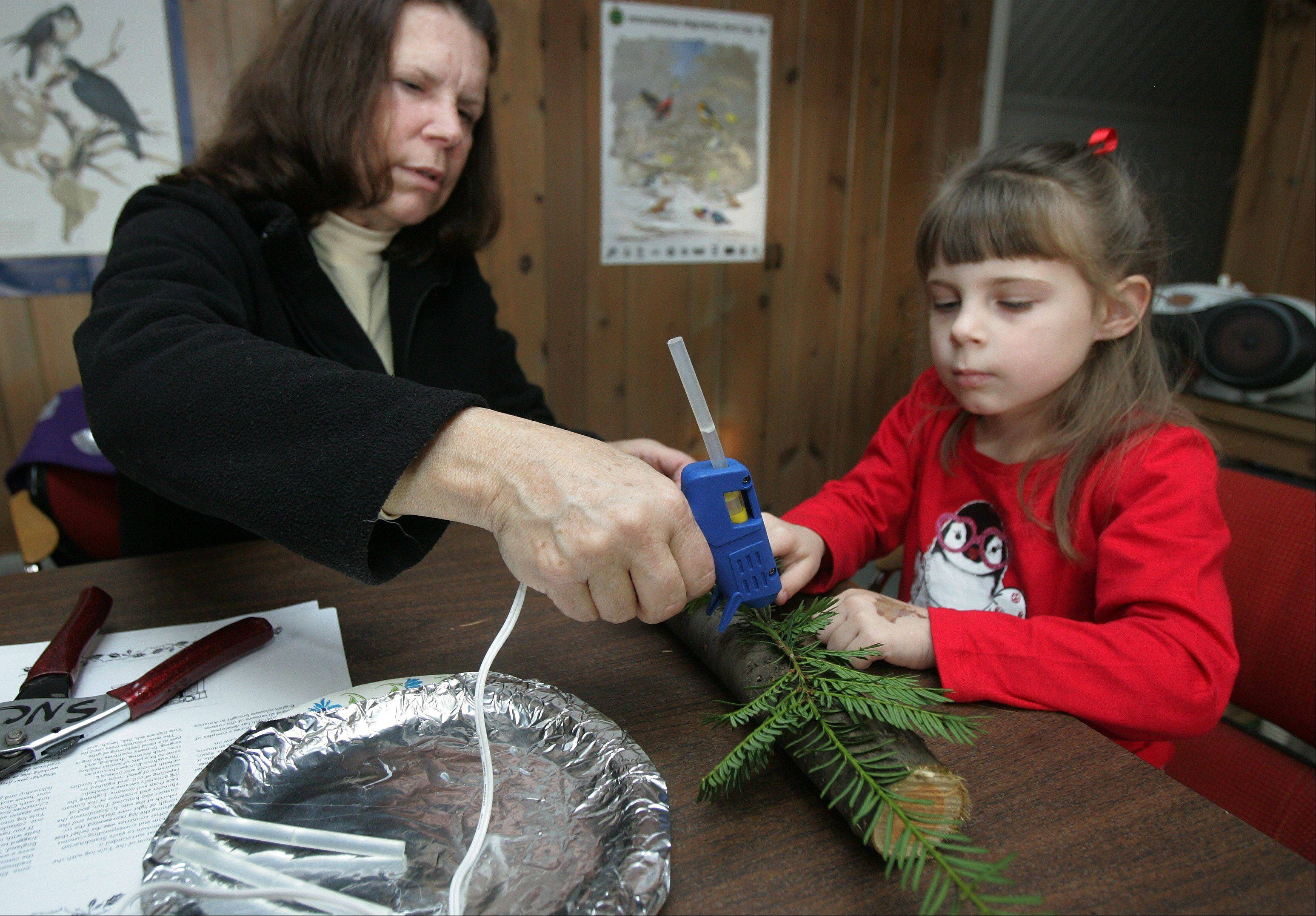 Laura Thome, of Algonquin, helps her granddaughter, Kayleigh DeGeorge, 4, put ornaments on her Yule log during the Yule Log Open House Sunday at the Stillman Nature Center in South Barrington. Visitors learned to make festive yule logs for decorations out of natural materials.