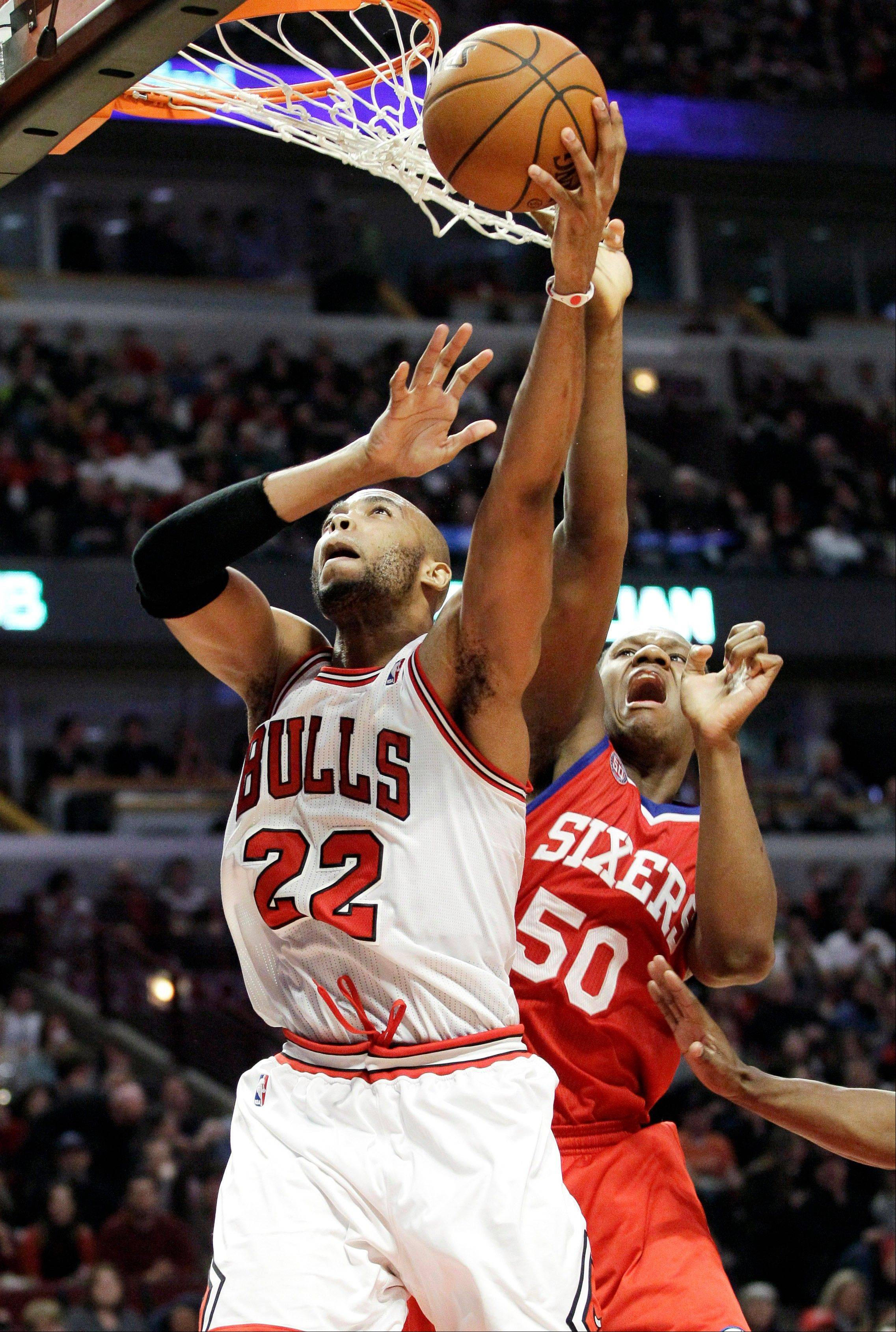 Bulls forward Taj Gibson, left, shoots against Philadelphia 76ers center Lavoy Allen during the second half of an NBA basketball game in Chicago on Saturday, Dec. 1, 2012. The Bulls won 93-88.