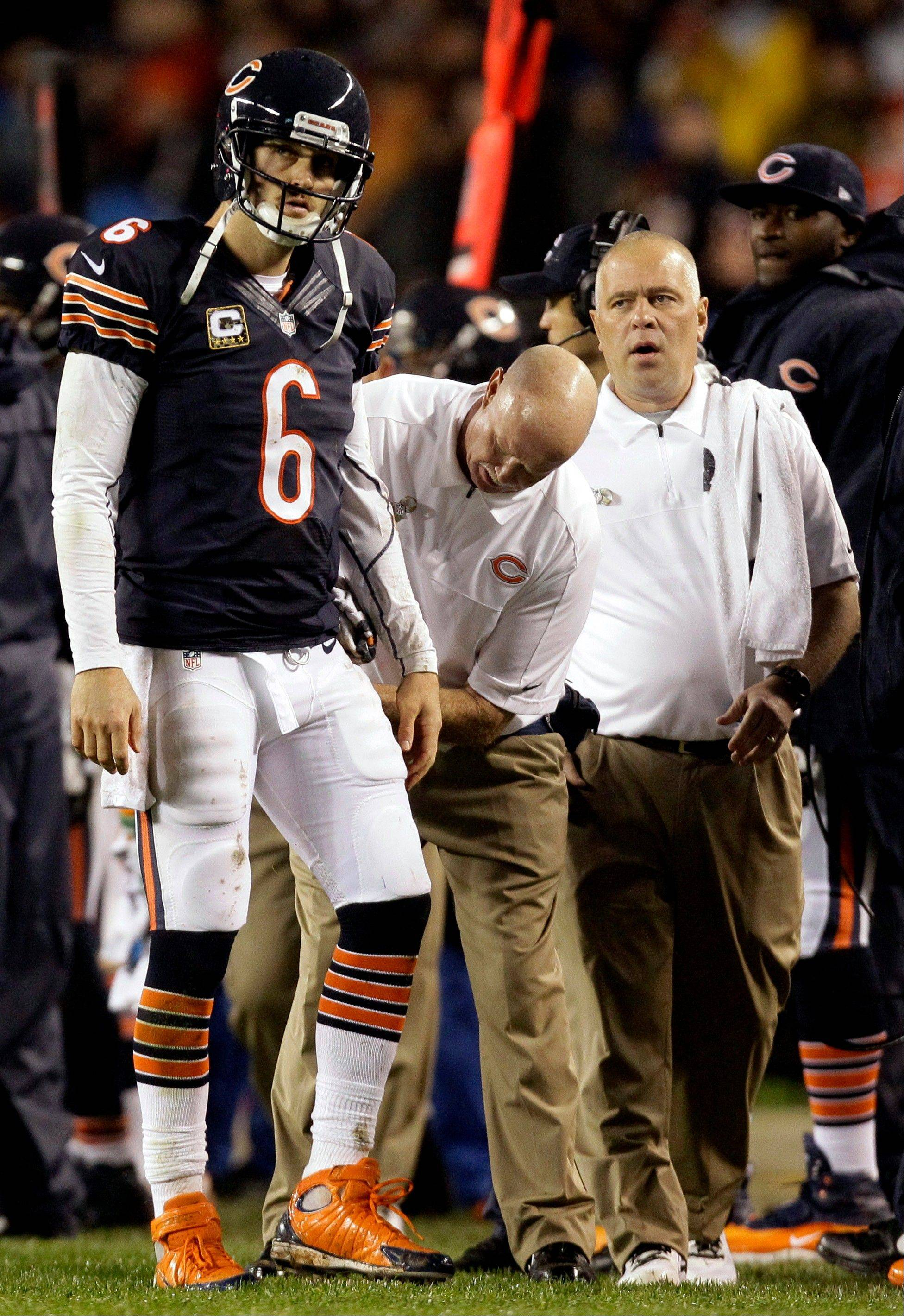 Trainers look at Bears QB Jay Cutler after Cutler took a late hit by Houston Texans linebacker Tim Dobbins. Cutler missed one game with a concussion but returned last week against the Vikings.