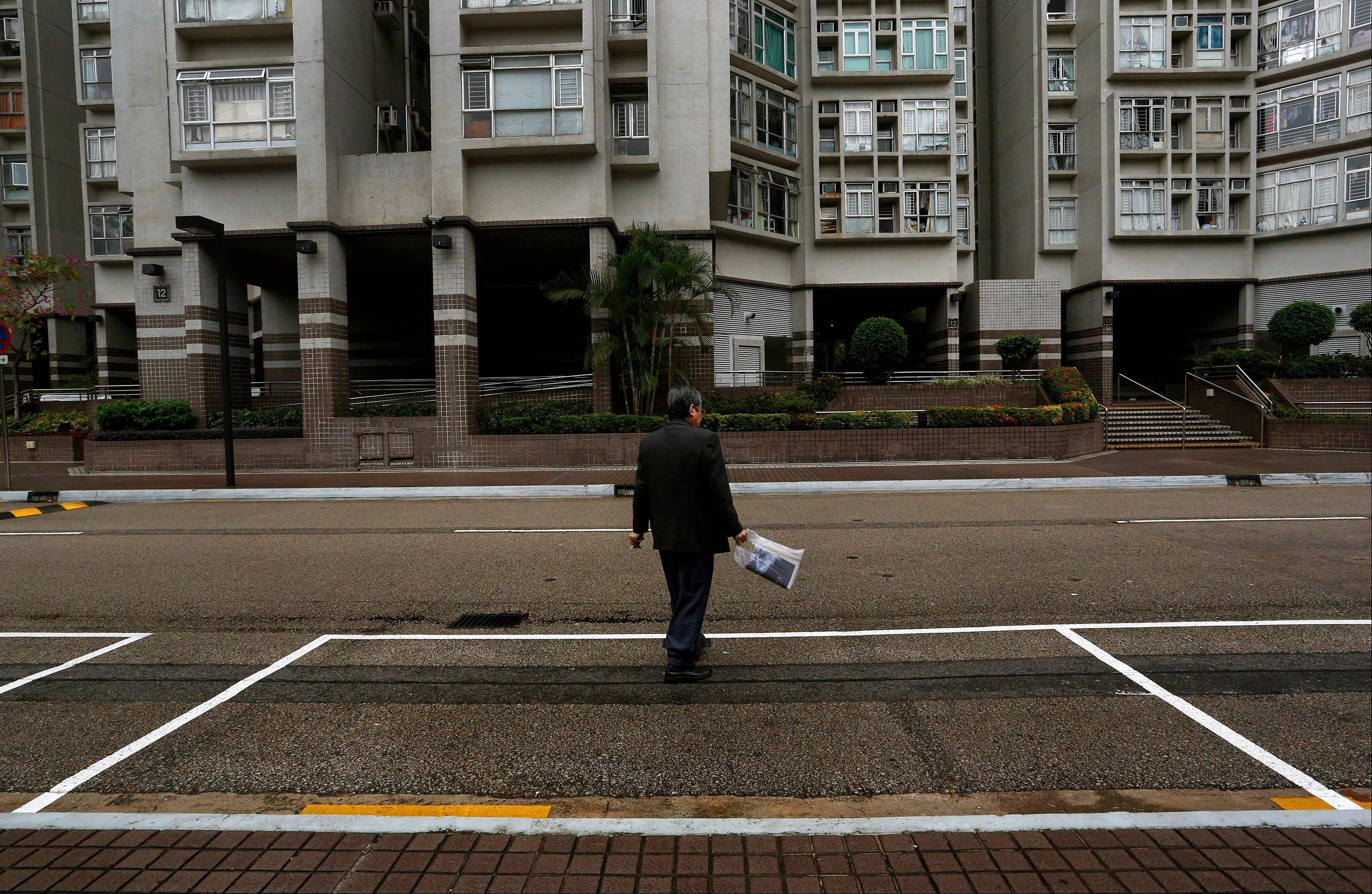 A man walks past a parking spot Tuesday outside a residential building in Hong Kong. Investors looking for new areas to park their cash in Hong Kong are driving up prices for parking spaces, sparking fears of a bubble in the Asian financial center. Prices for parking spots in Hong Kong are nearing historic highs, the side effect of government curbs to cool the housing market amid worries of overheating following the latest round of economic stimulus in the U.S.