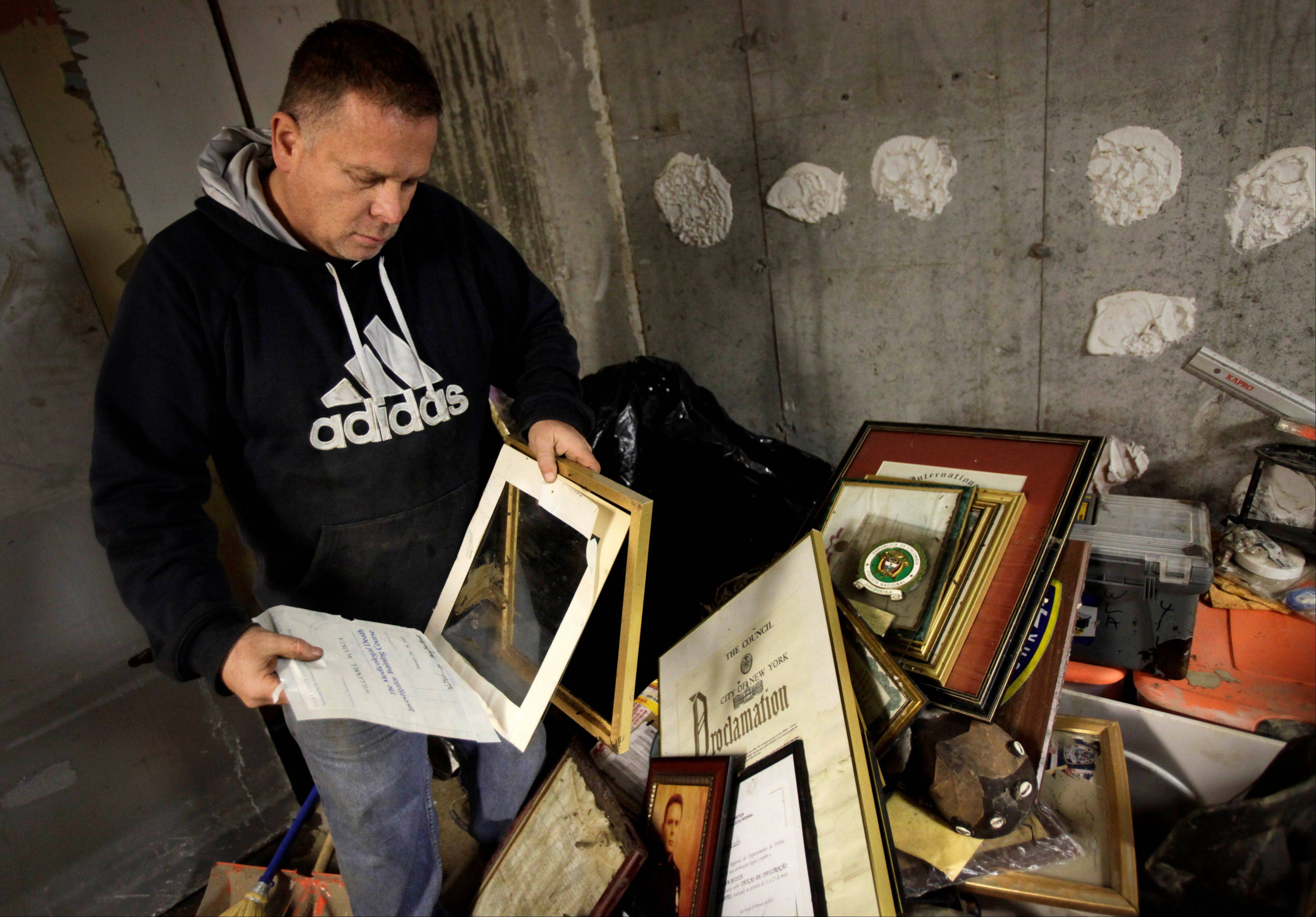 Bill Acosta sorts Tuesday through his numerous diplomas, awards and other important documents in his basement office on the Rockaway Peninsula in Queens, New York. Acosta, who is a veteran and has a long record of government service, is upset that FEMA or any other government agency was unable to offer him financial assistance.