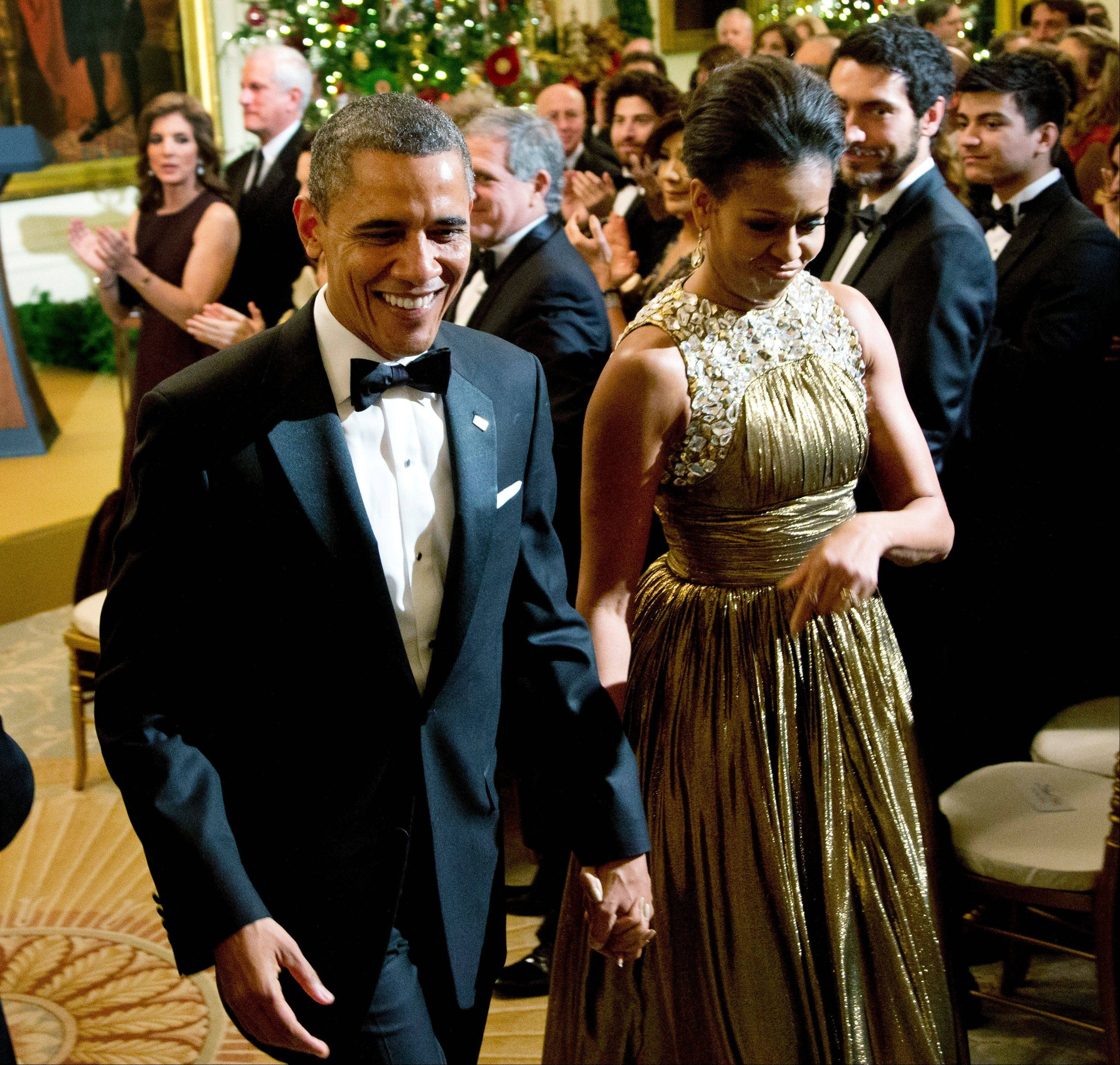 President Barack Obama and first lady Michelle Obama leave a reception in honor of the 2012 Kennedy Center Honors recipients in the East Room of the White House Sunday. At the back left is Caroline Kennedy.