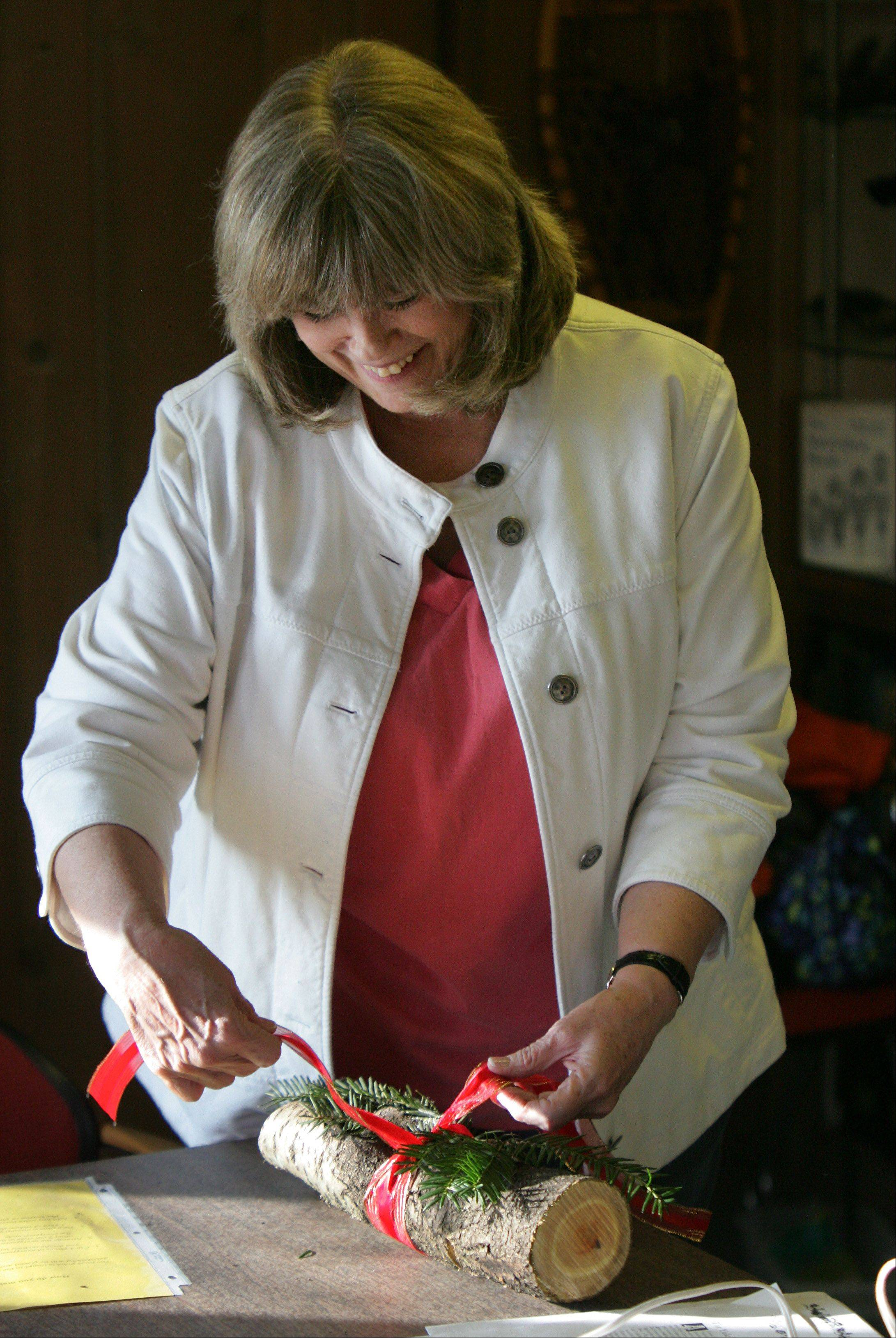 Volunteer Joanne Strong of Hoffman Estates demonstrates how to make a decorative Yule log during the Yule Log Open House Sunday at the Stillman Nature Center in South Barrington. Visitors learn to make festive Yule logs out of natural materials.