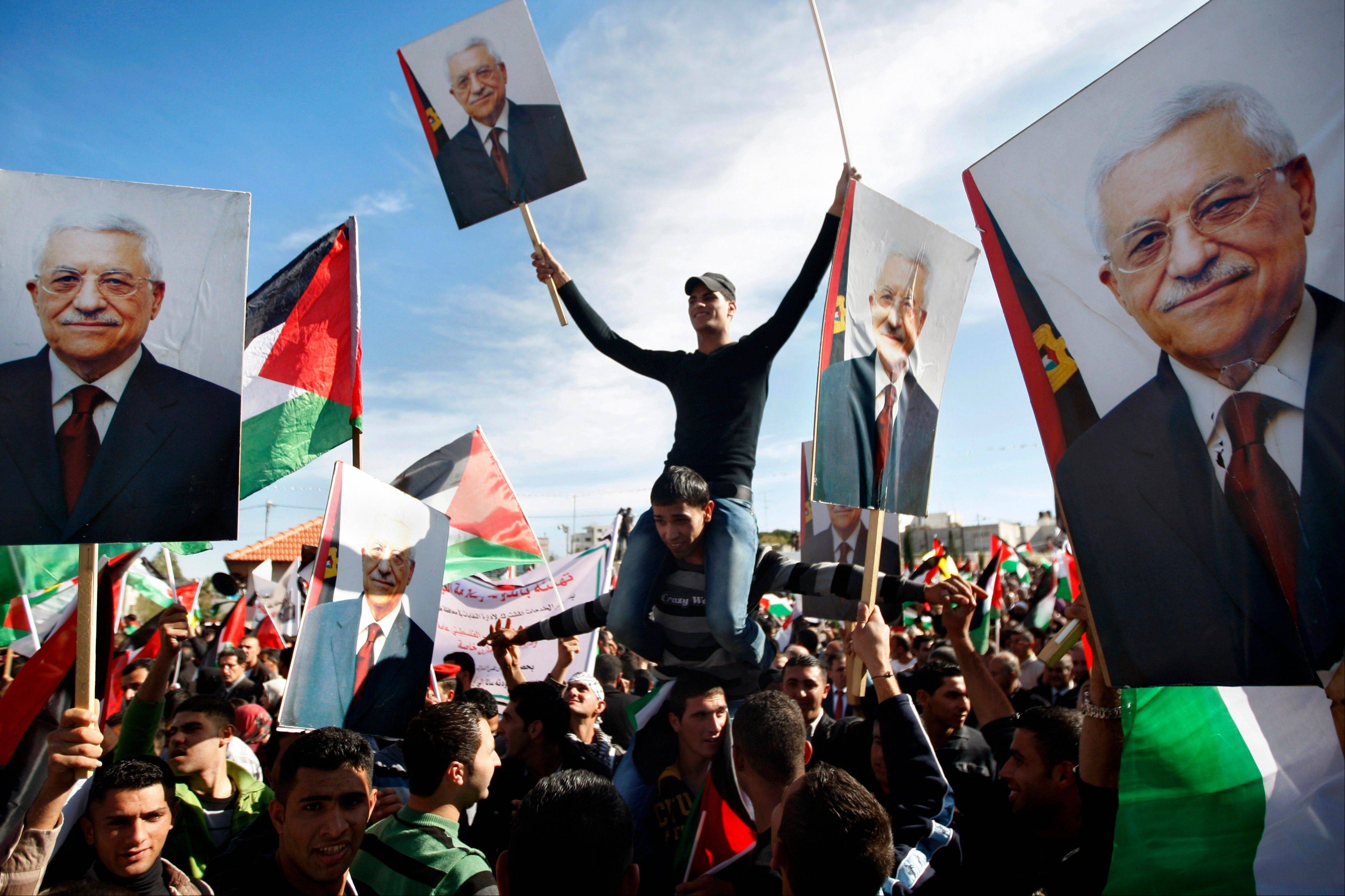 Palestinians hold pictures of Palestinian President Mahmoud Abbas, as they celebrate their successful bid to win U.N. statehood recognition in the West Bank city of Ramallah on Sunday.