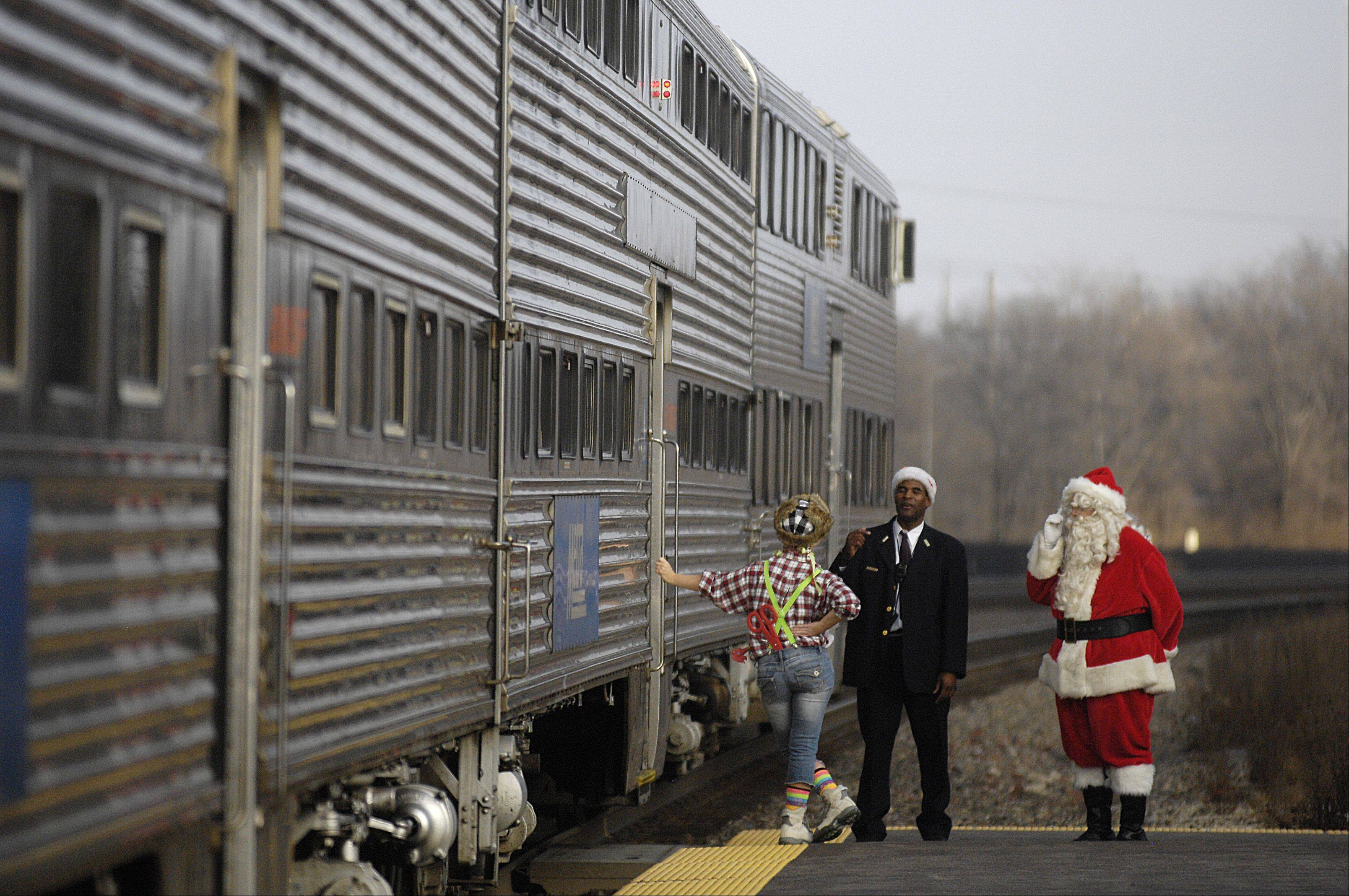 "Santa waits on the Lisle Metra platform Sunday before boarding the Polar Express train heading to the ""North Pole"". The ""Polar Express"" was not directly connected to Lisle's Once Upon a Christmas celebration at Lisle Station Park, but the timing of the train and festival made it possible for visitors to participate in both events."