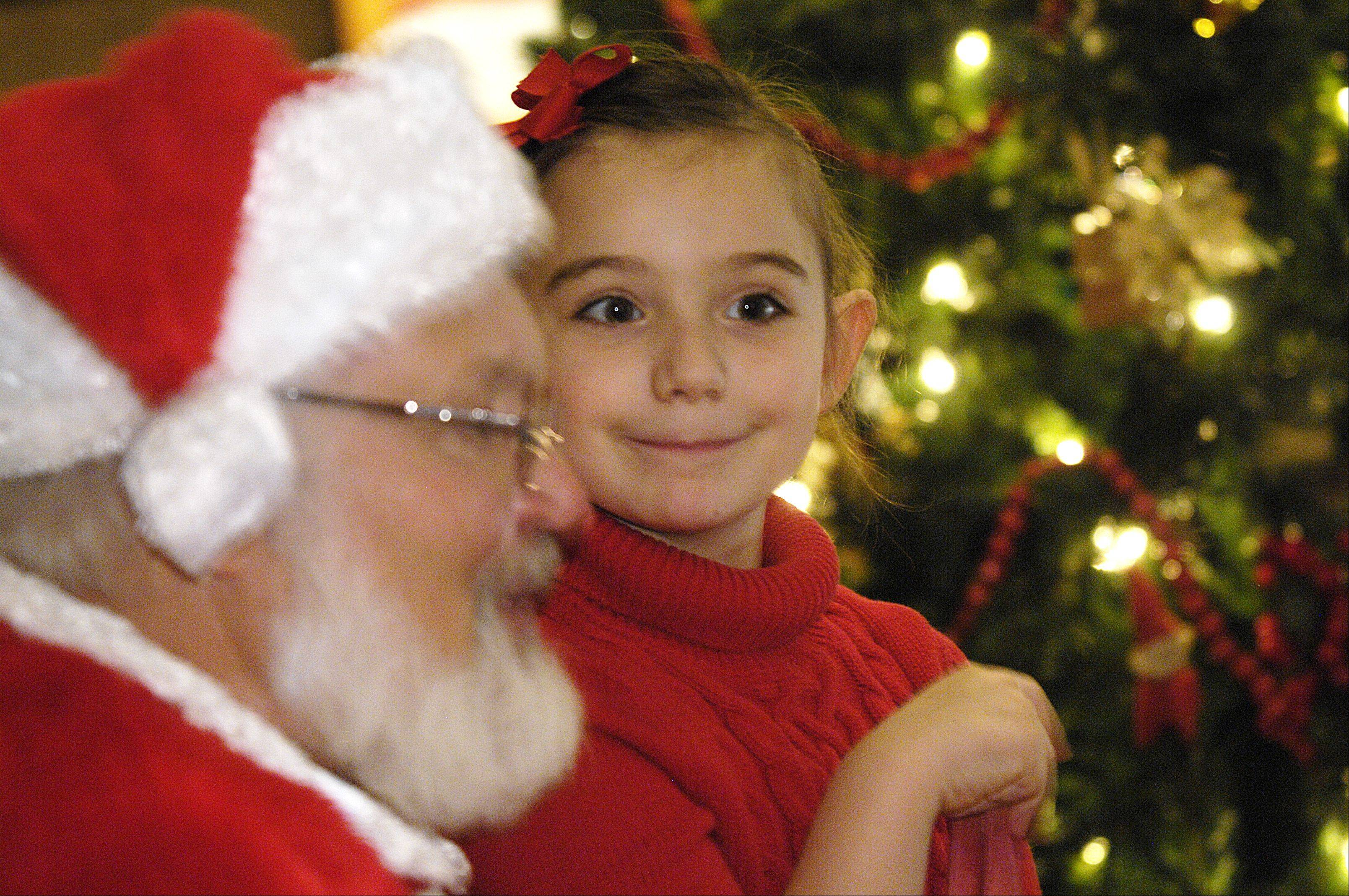Claire Weissenth, 6, of Geneva, visits with Santa during Lisle's Once Upon a Christmas celebration Sunday at Lisle Station Park.