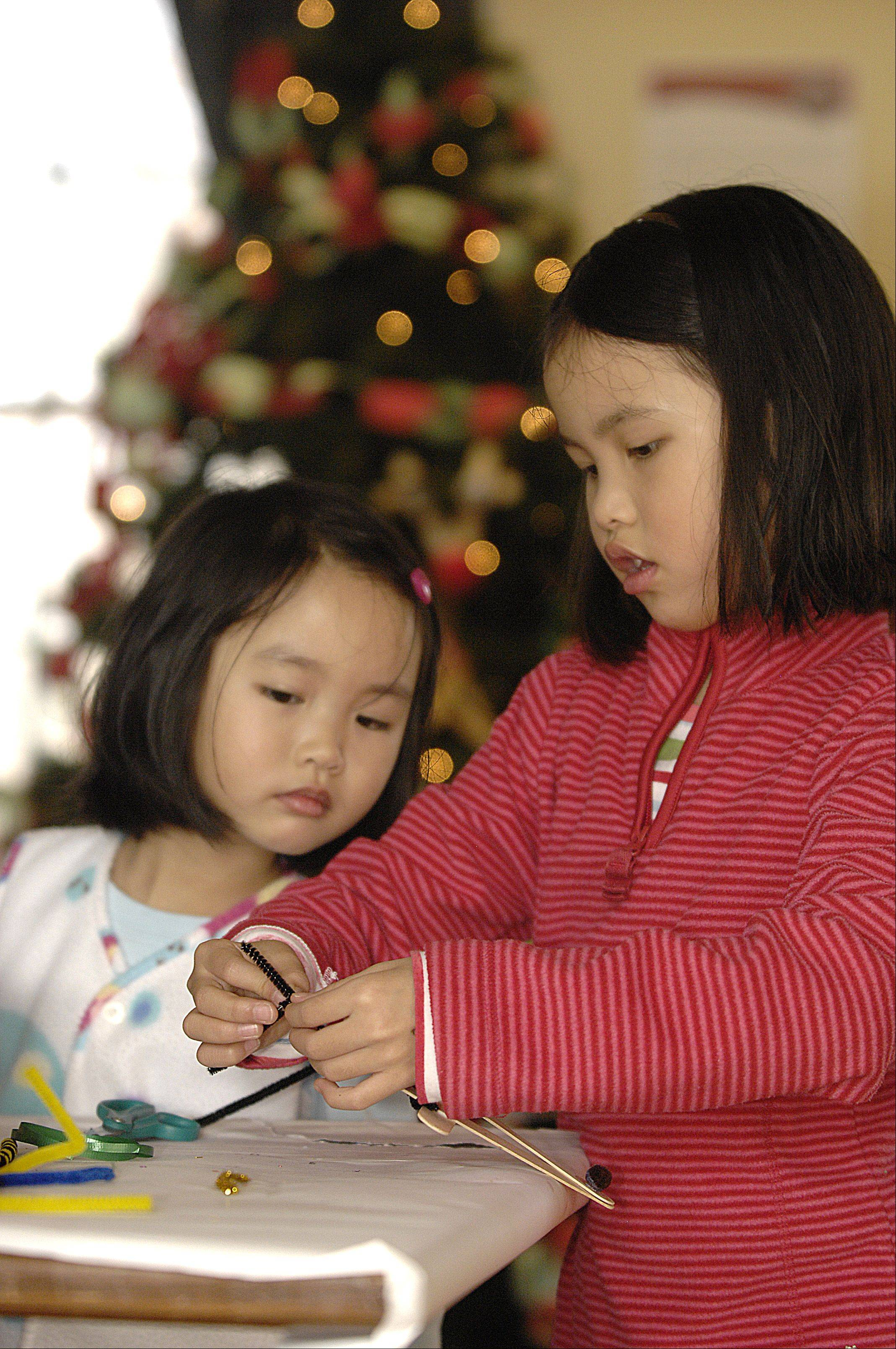 Sophie Mui, 4, and her sister Adelyn, 7, of Lisle, work on a reindeer ornament Sunday during Lisle's Once Upon a Christmas celebration at Lisle Station Park.