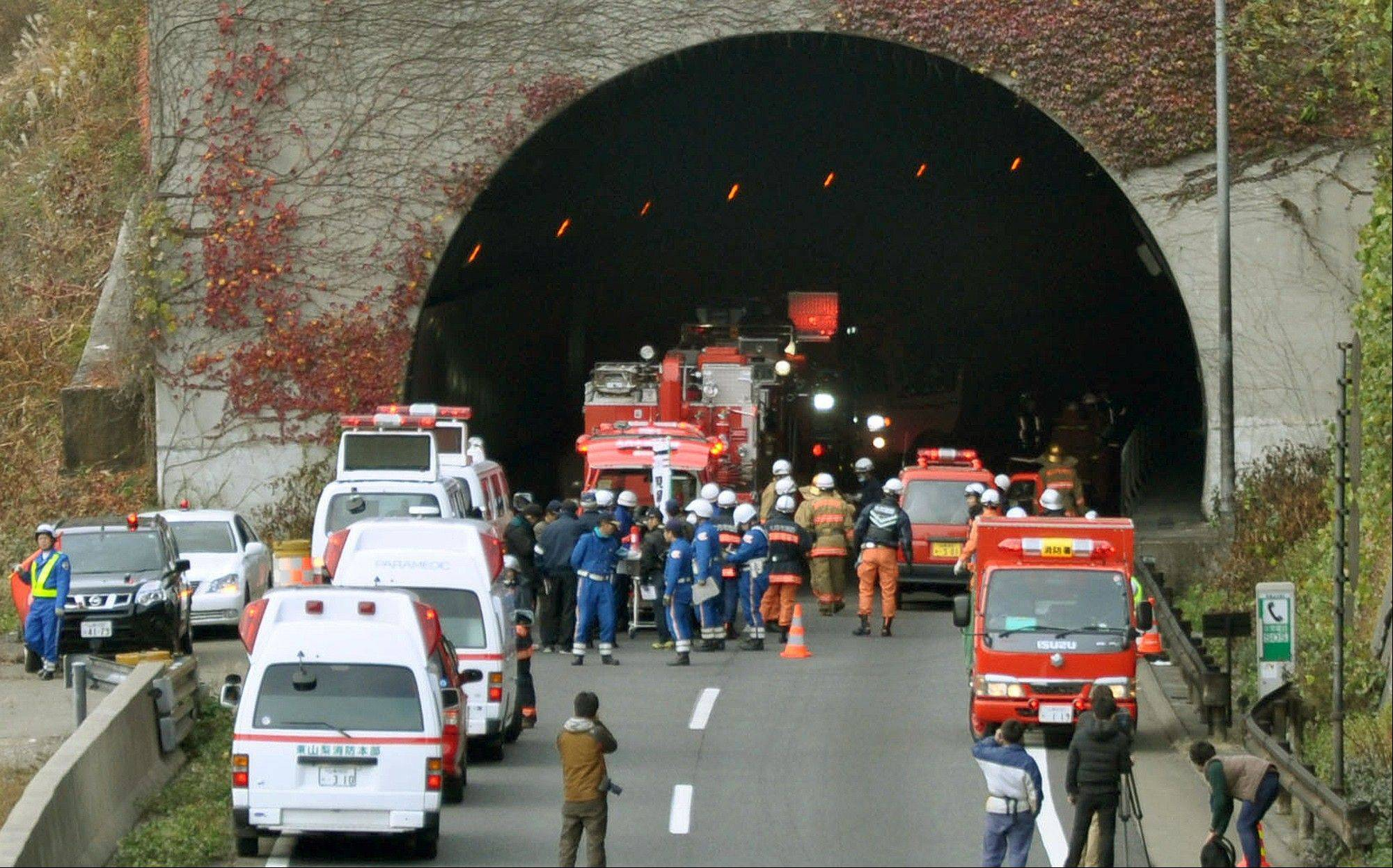 Police officers and firefighters gather Sunday at the exit of the Sasago Tunnel on the Chuo Expressway in Otsuki, Yamanashi Prefecture, central Japan. Police said that parts of the tunnel collapsed Sunday morning, trapping an unknown number of vehicles as smoke from a fire inside prevented rescuers from approaching.