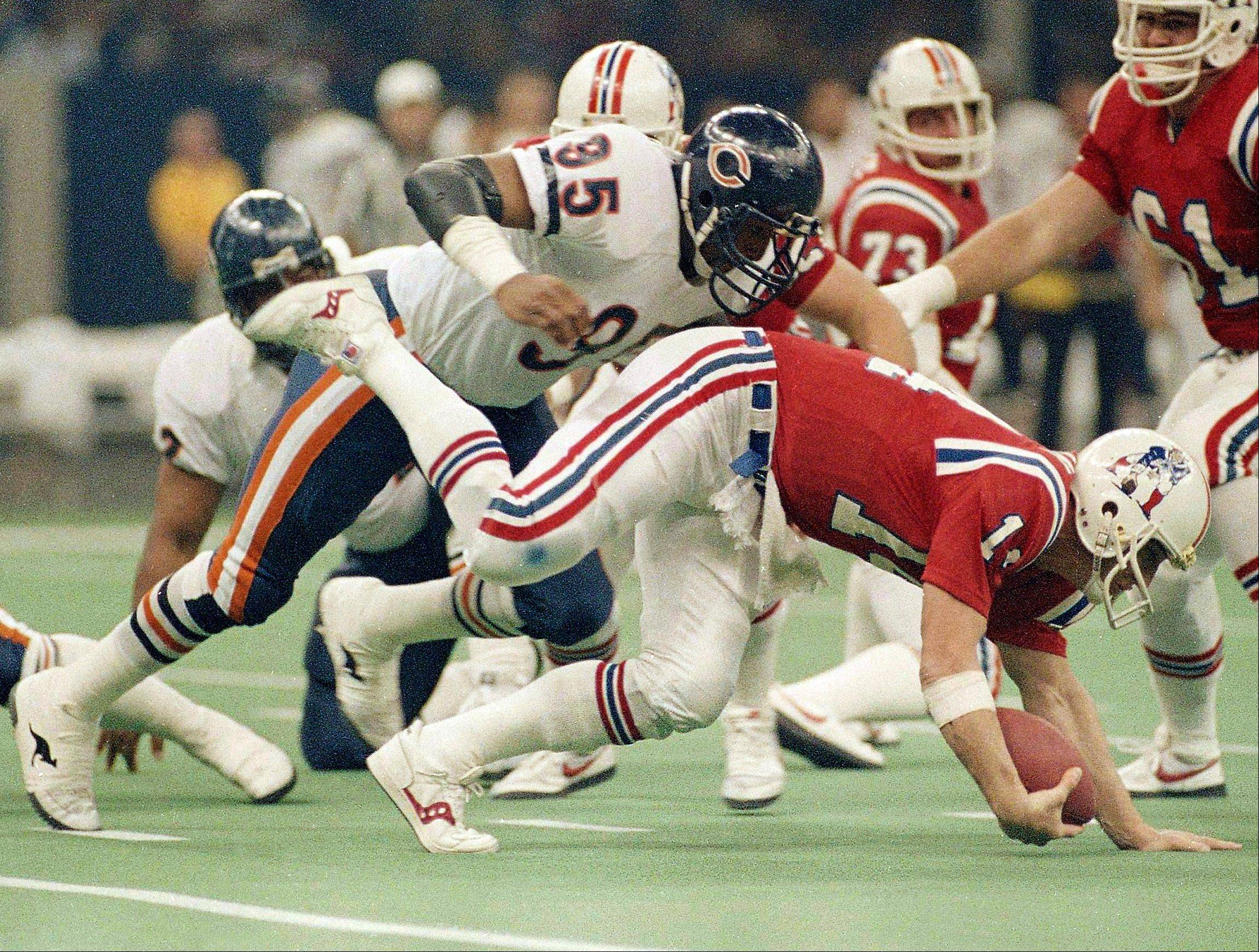 In the New England backfield for much of the game, Bears defensive end Richard Dent sacks Patriots' quarterback Steve Grogan during the Super Bowl XX football game in New Orleans. The Bears won 46-10 and Dent was named most valuable player of the game.