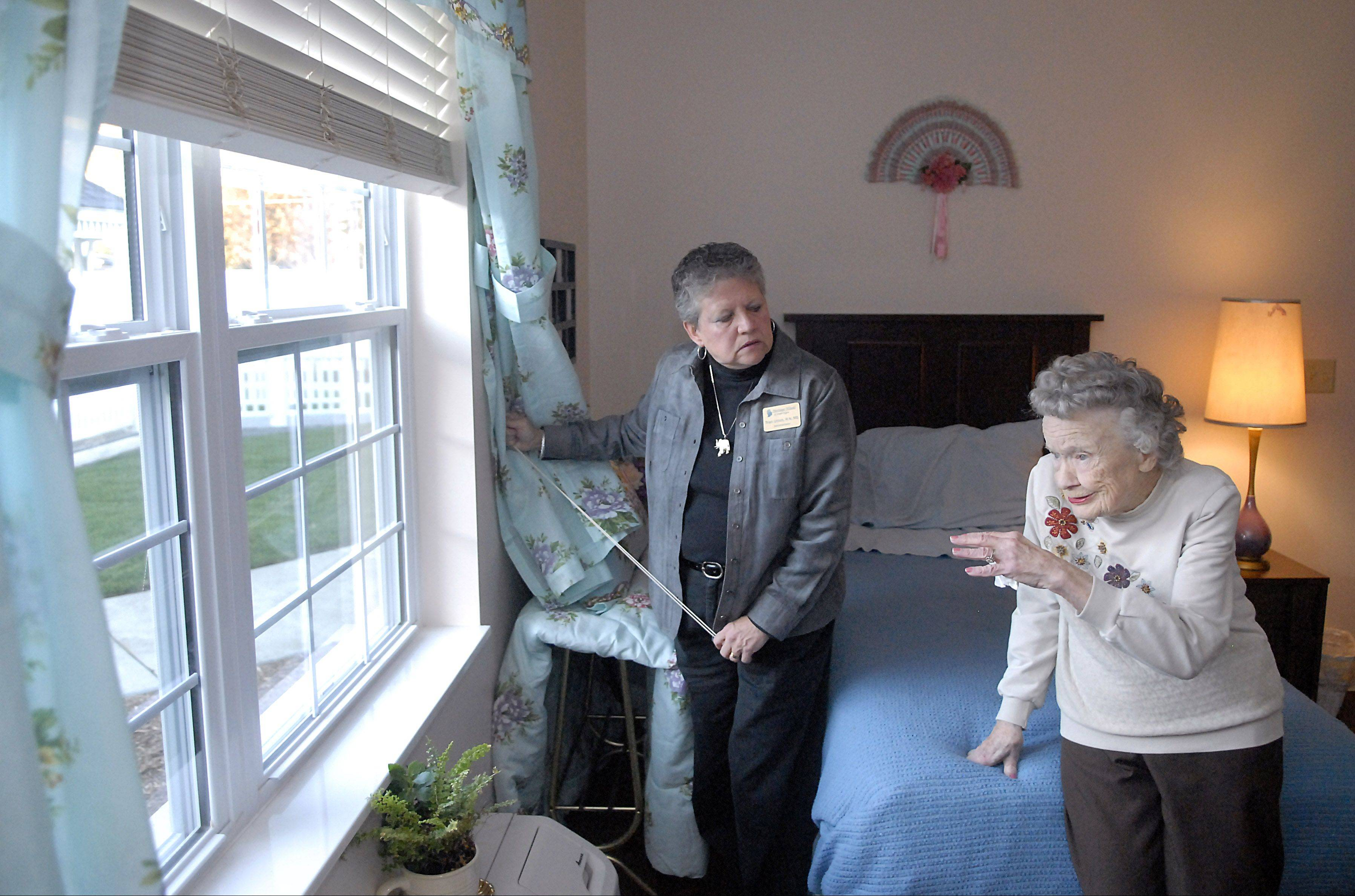 Trish Uttich, White Oaks administrator and registered nurse, listens to resident Almira Behrendt talk about the view from her window at the memory care living facility in South Elgin.