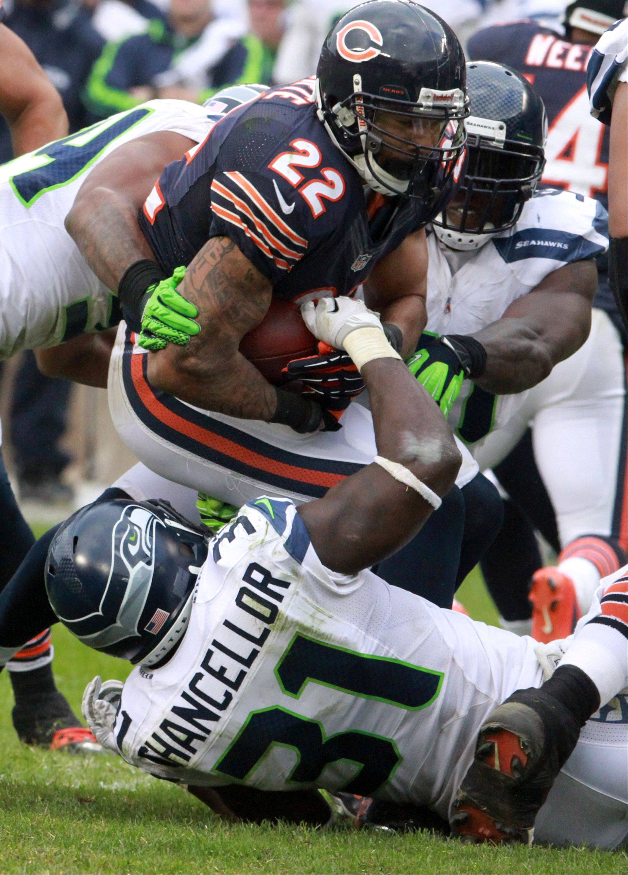 Matt Forte is dragged down by a host of Seahawks at Soldier Field on Sunday.