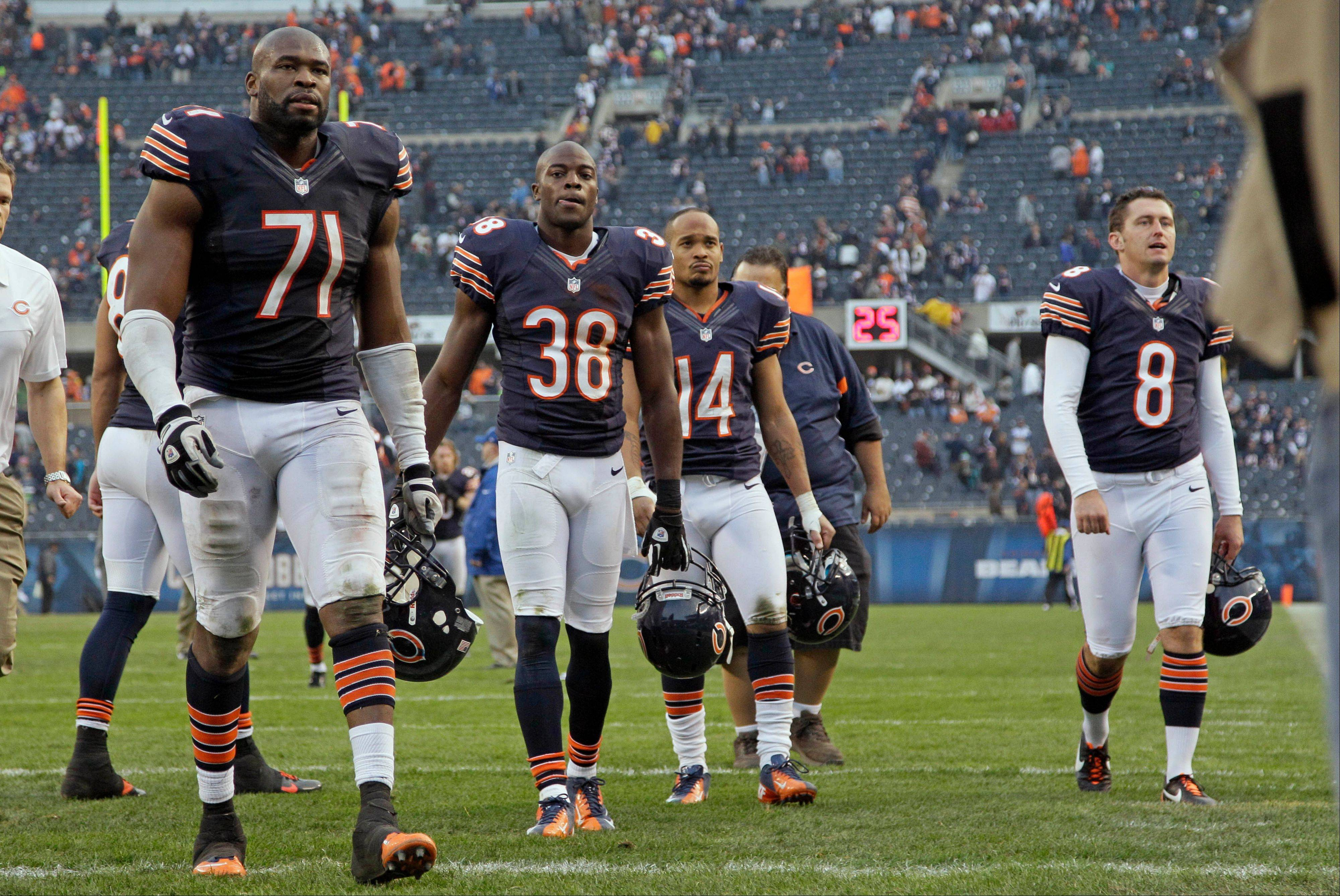 Israel Idonije (71), Zack Bowman (38), Eric Weems (14) and Adam Podlesh (8) walk off the field after the Bears' 23-17 loss in overtime to Seattle on Sunday at Soldier Field.