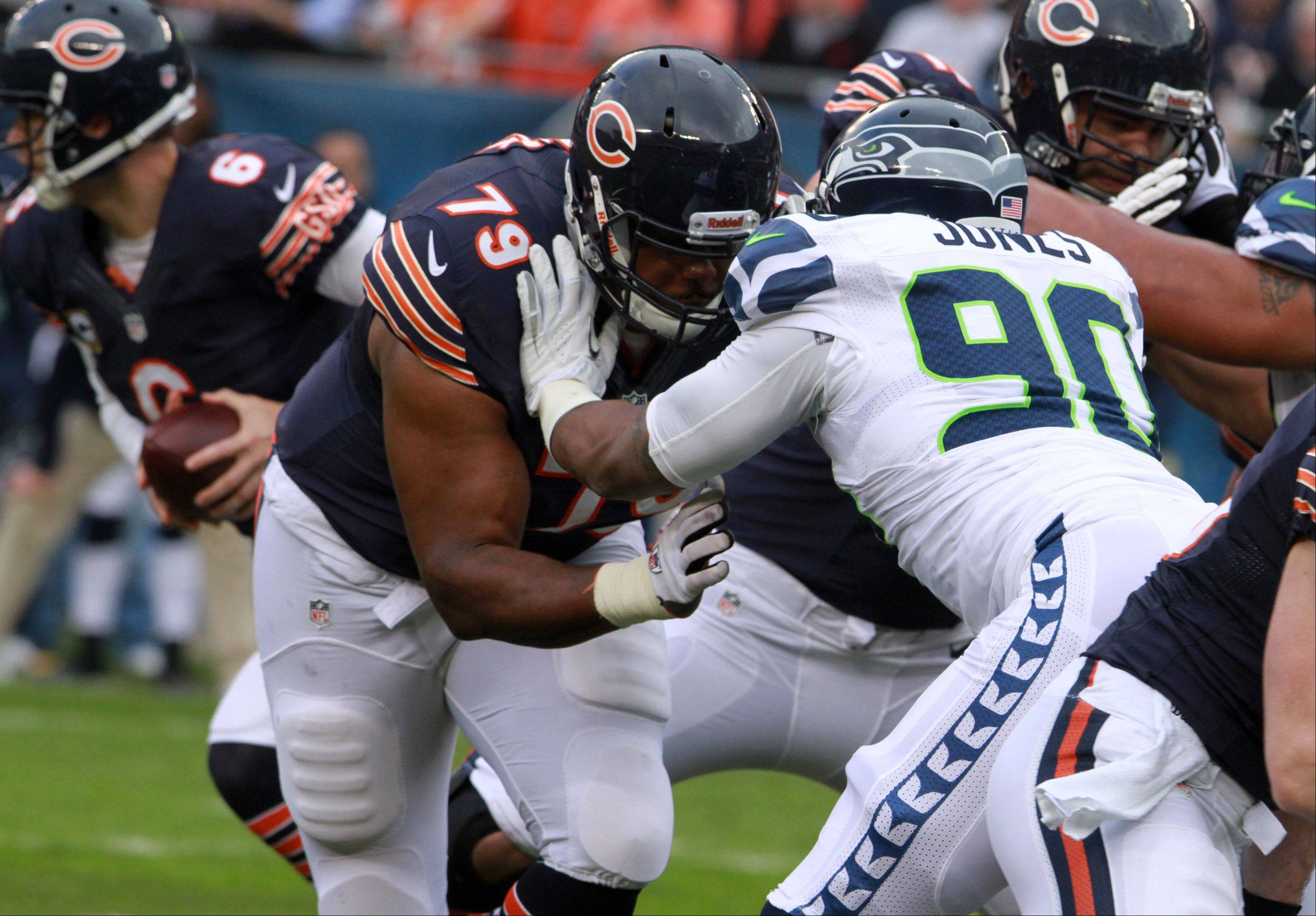 Chicago Bears tackle Jonathan Scott blocks Seattle Seahawks defensive end Jason Jones as Cutler looks to hand the ball off at Soldier Field on Sunday.