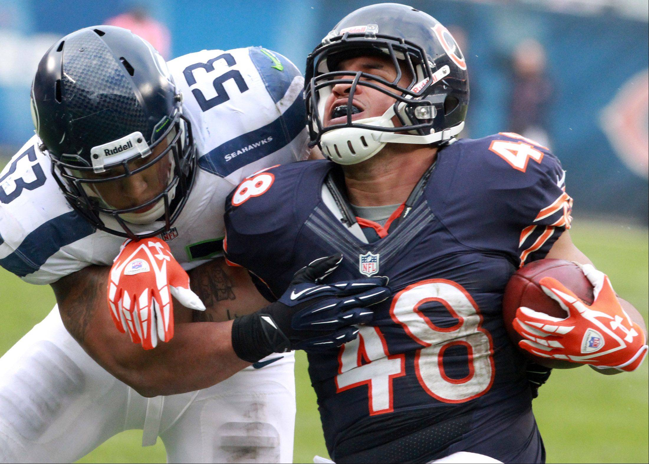 Chicago Bears fullback Evan Rodriguez is pulled down by Seattle Seahawks linebacker Malcolm Smith at Soldier Field on Sunday.