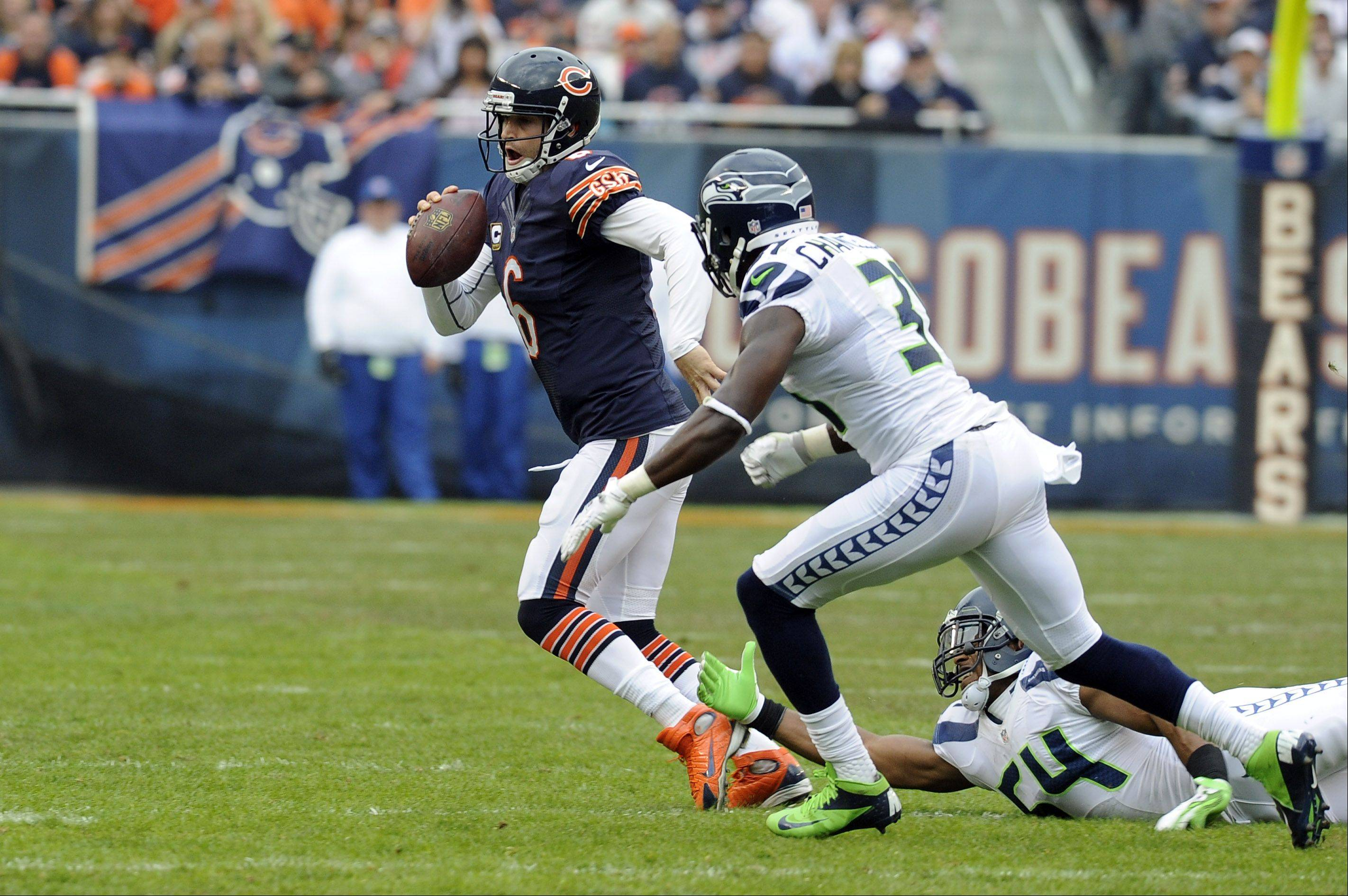 Bears quarterback Jay Cutler on the run in the first half from Seahawks Kam Chancellor as he gains yards and everyone holds their breath at Soldier Field in Chicago.