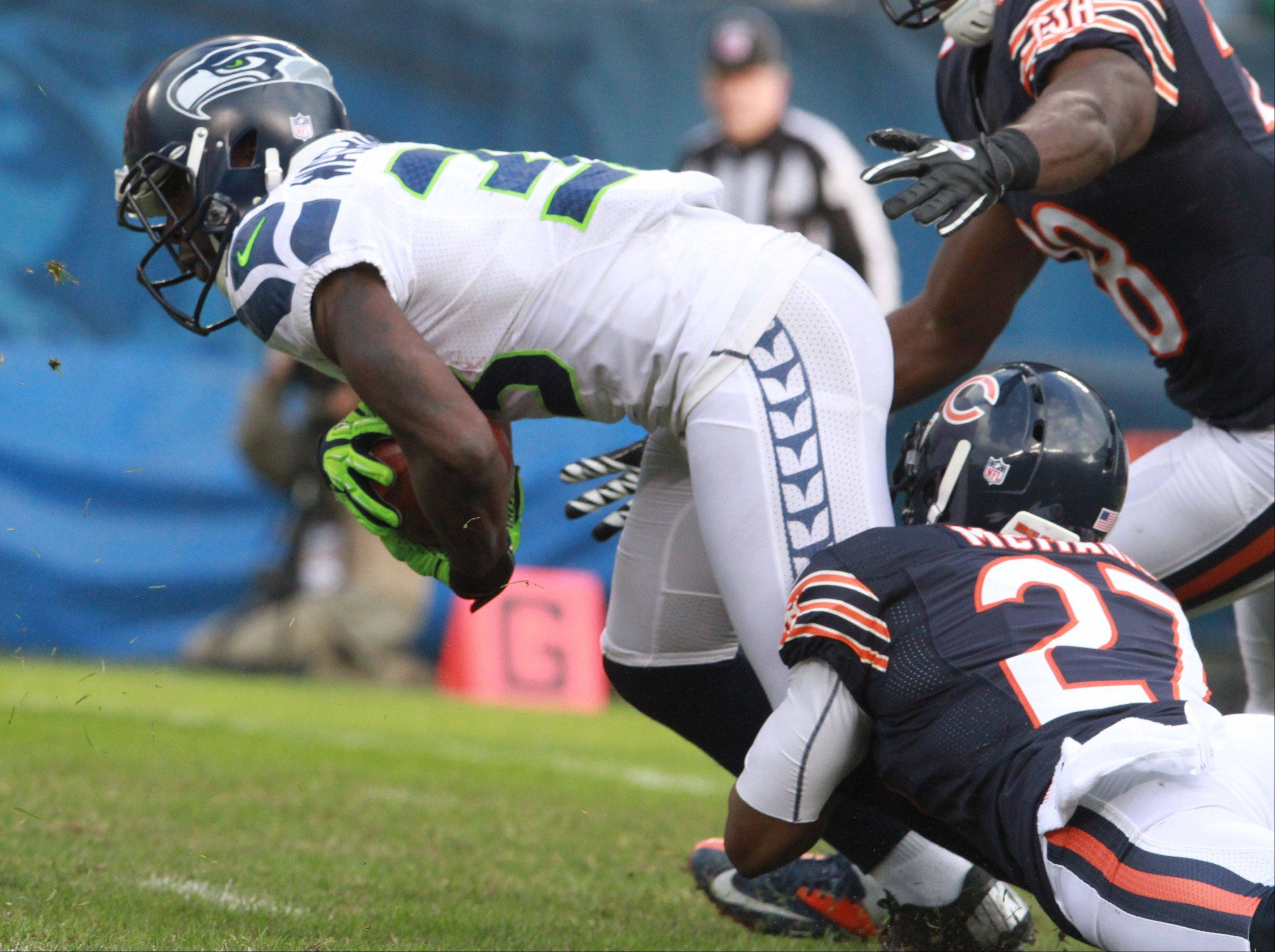 Seattle Seahawks running back Leon Washington is tripped up by Chicago Bears defensive back Sherrick McManis at Soldier Field on Sunday.
