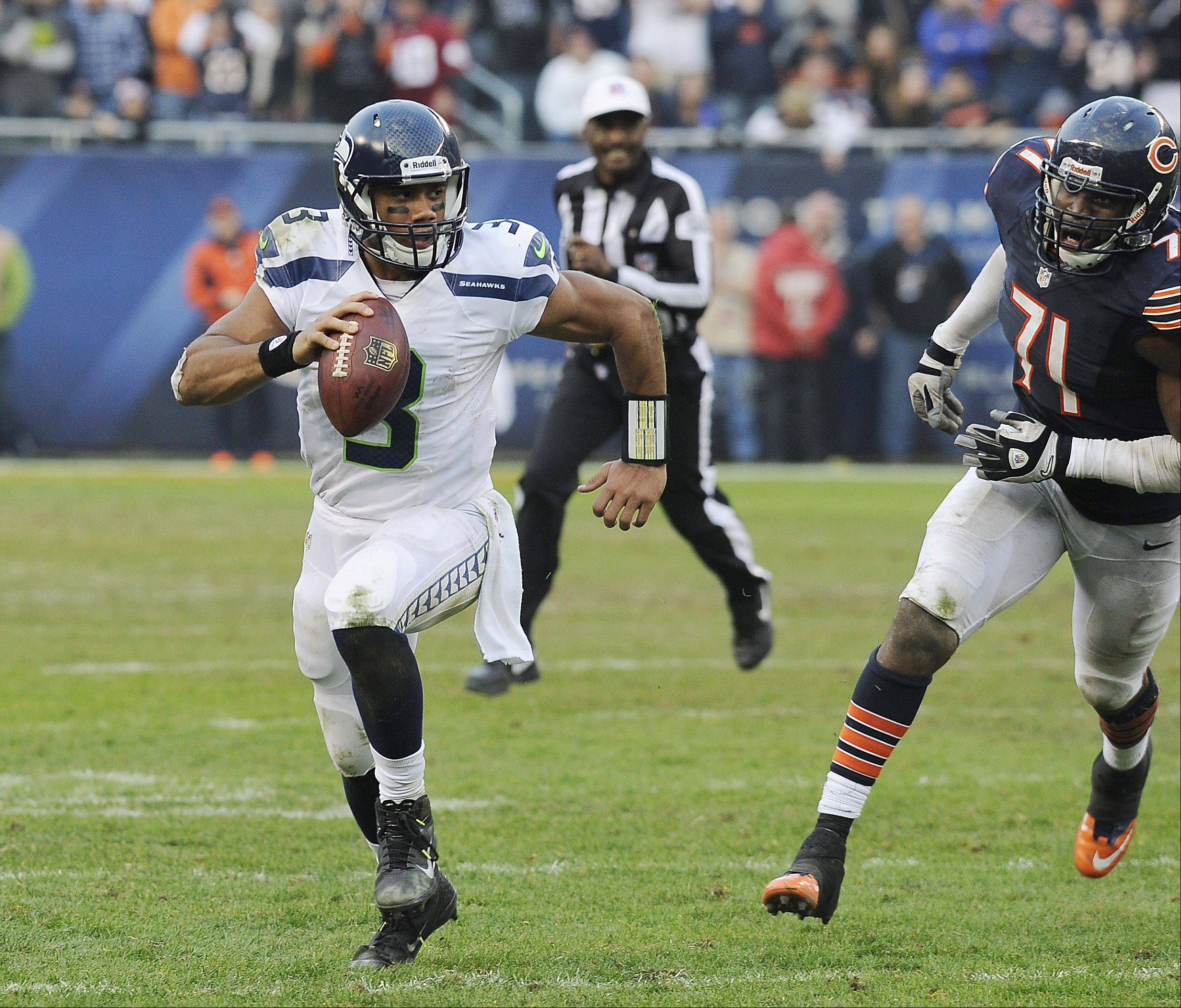 Seahawks quarterback Russell Wilson on the run in the 4th from Bears Israel Idonije as the Bears fall to the Seahawks in overtime 23-17 at Soldier Field in Chicago.