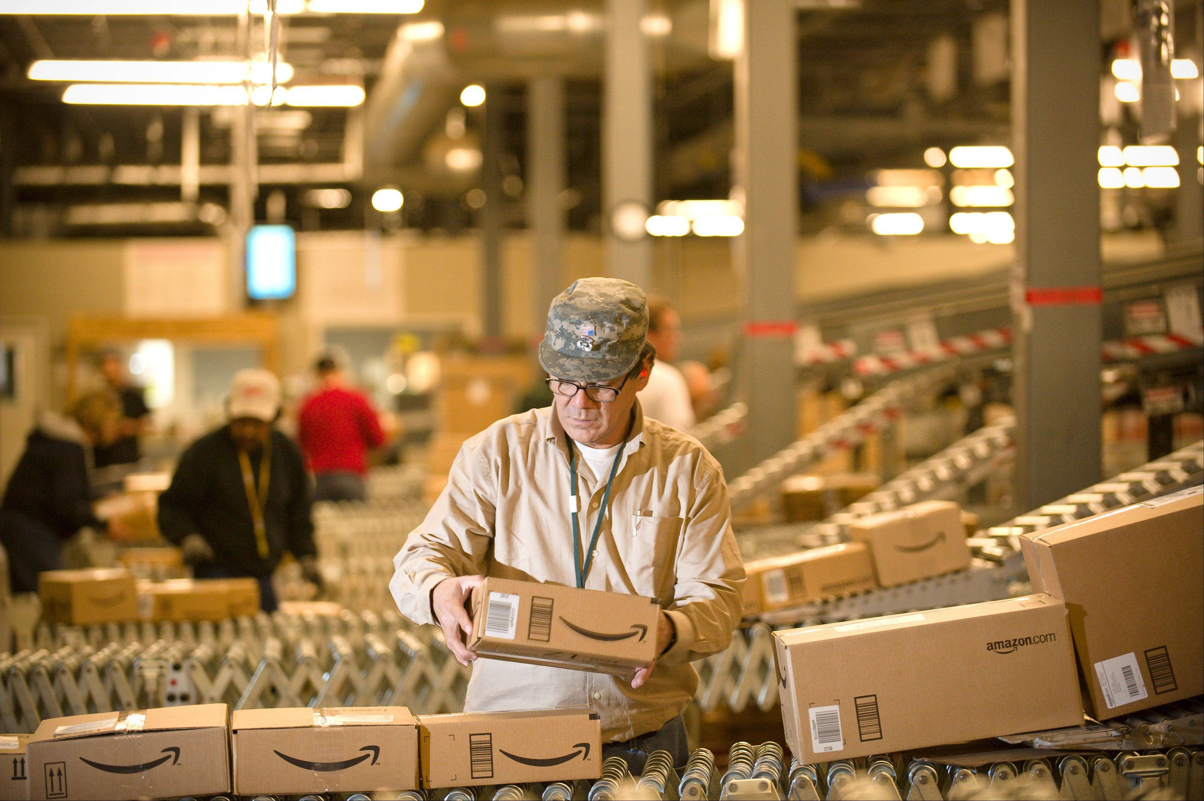 An Amazon.com employee processes orders at its Fernley, Nev., warehouse. A storm is brewing in Europe over how little Internet powerhouses like Google and Amazon are paying in tax.
