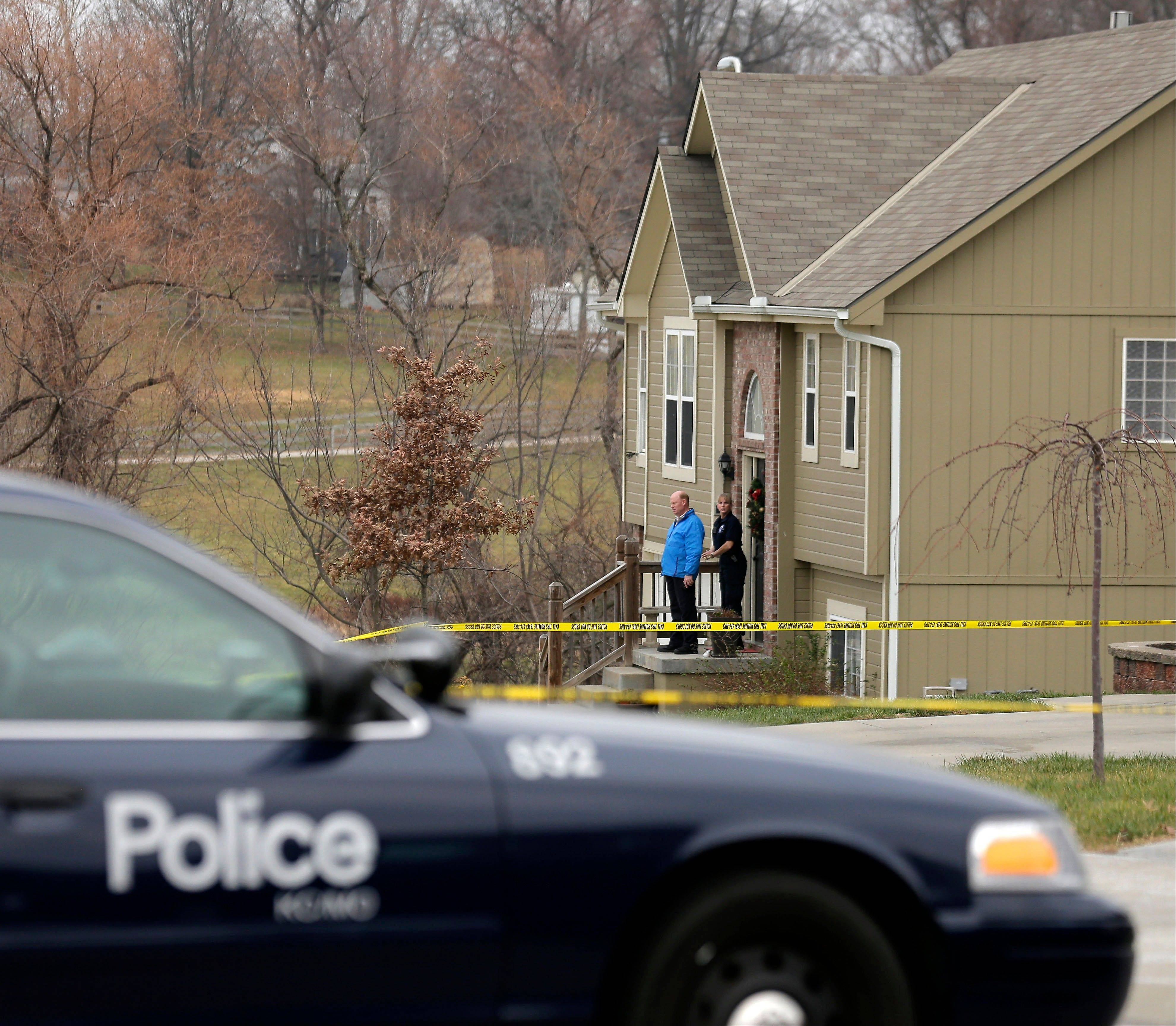 Investigators stand outside an Independence, Mo., house where police say Kansas City Chiefs linebacker Jovan Belcher fatally shot his girlfriend Saturday before driving to the NFL football team�s training facility and shooting himself.