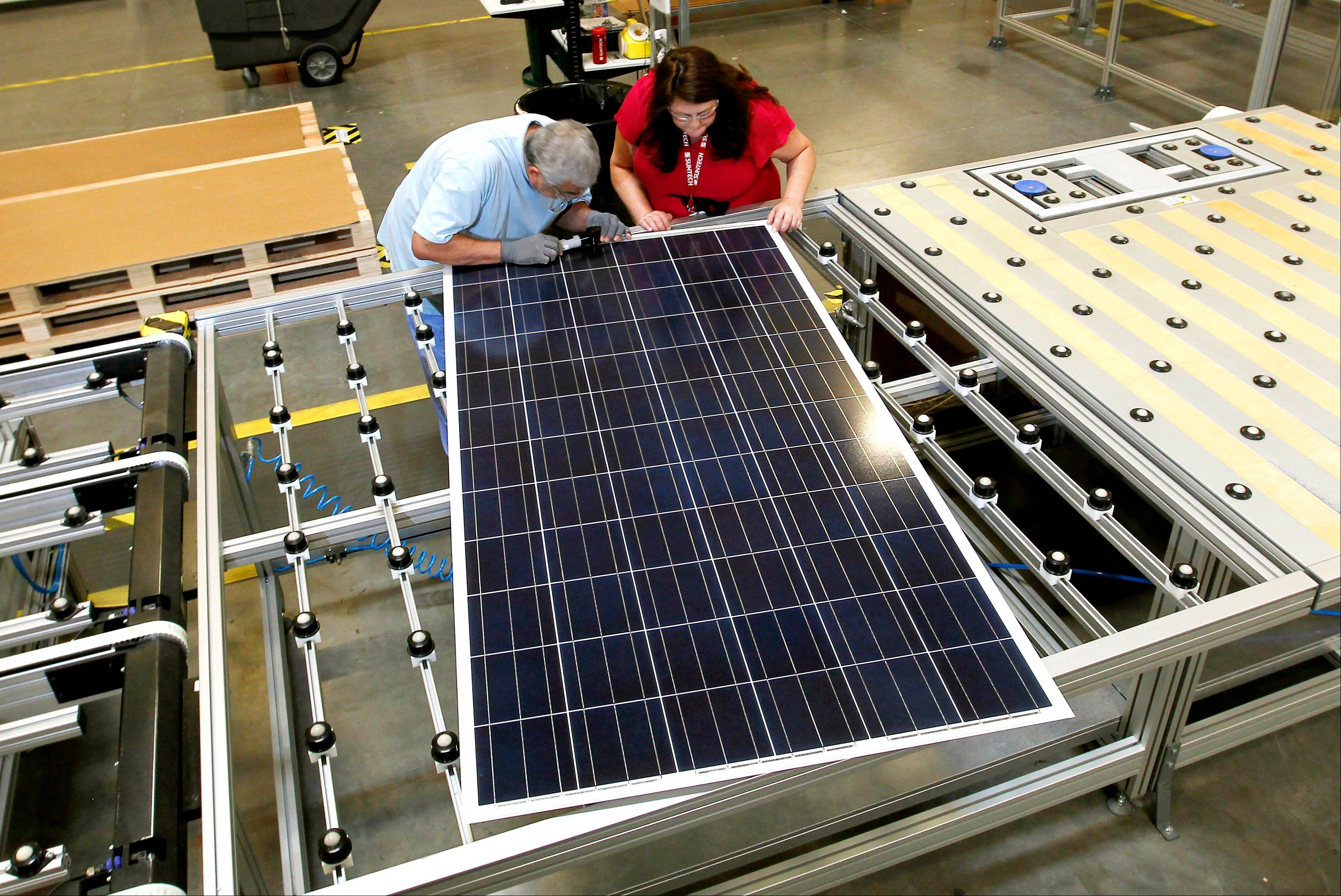 A worker for a Chinese-owned solar panel manufacturer examines a solar panel at a company facility in Goodyear, Ariz. The factory makes solar panels for one of the world's biggest solar manufacturers.