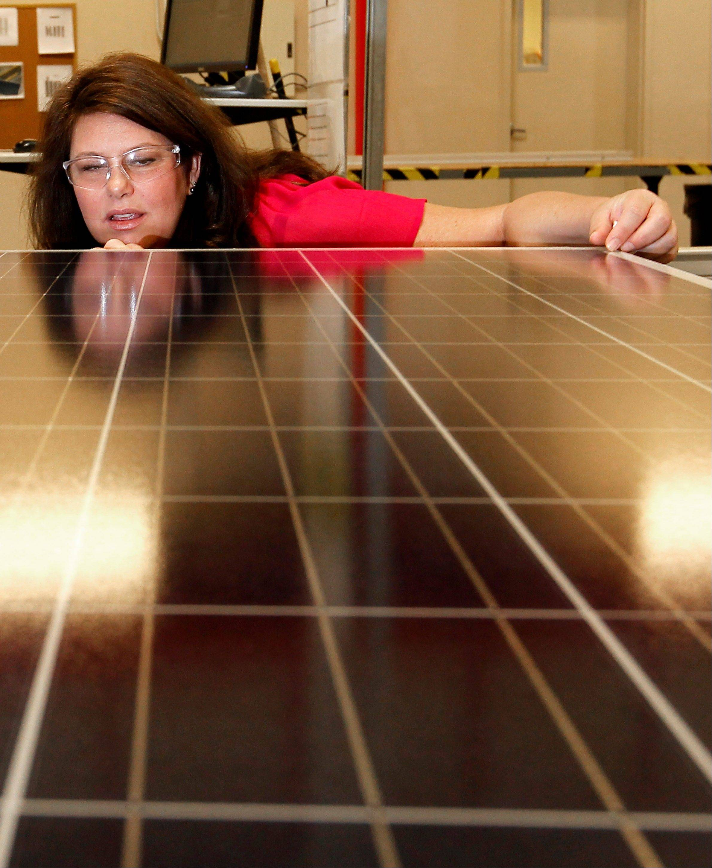 tacey Rassas, a quality control manager at Suntech Power Holdings Co., a Chinese-owned solar panel manufacturer, examines a solar panel at a company facility in Goodyear, Ariz. The factory makes solar panels for one of the world's biggest solar manufacturers.