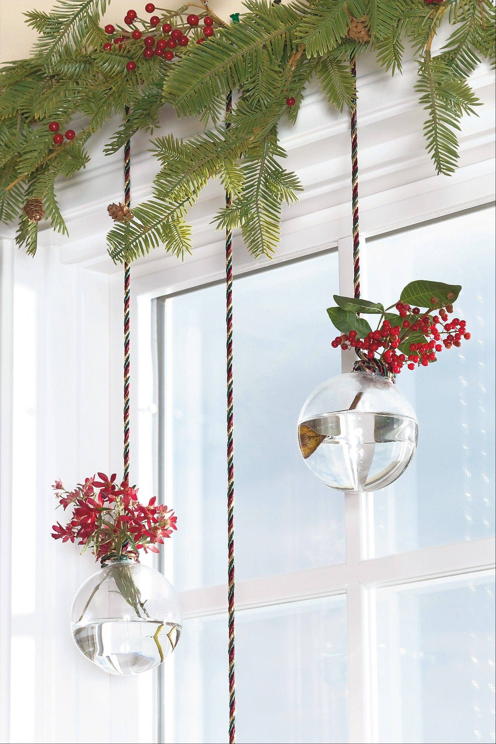 7. Dangling delights: Want something lovely to look at while you're washing dishes or rolling cookie dough? Embellish your windows with see-through ornaments filled with flowers. First, remove the ornaments' hooks or metal tops. Cut a length of holiday-hued cording, and hot glue one end of the cord around the ornament's neck. Trim the cording to the desired length. Fill the ornament with a small amount of water and add flowers or greenery. Knot the unglued cord end for security, and tack it to the window trim. Repeat for remaining ornaments. Vary the look by staggering the ornaments' heights or by opting for colored balls dangling from metallic ribbons.