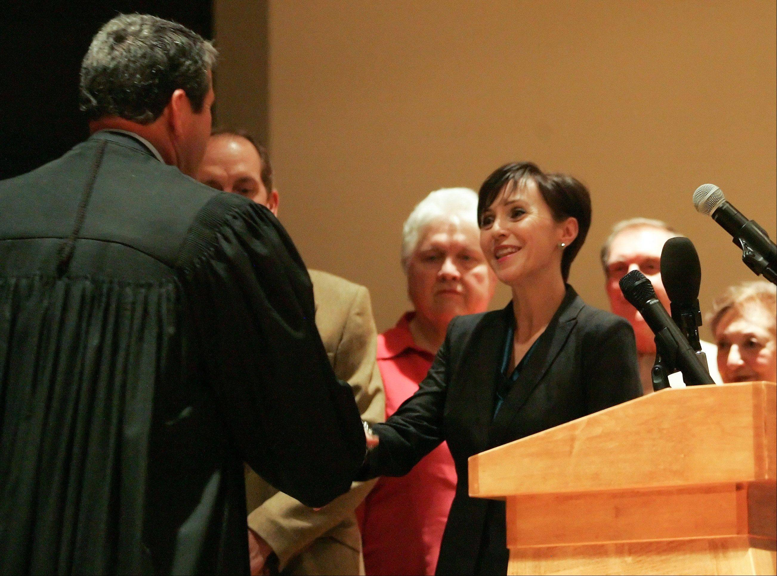 Elizabeth Chaplin is congratulated by Judge John Elsner after being sworn in as a District 2 county board member during the 2012 Inauguration of DuPage County elected officials at the Jack T. Knuepfer Administration building in Wheaton on Monday.