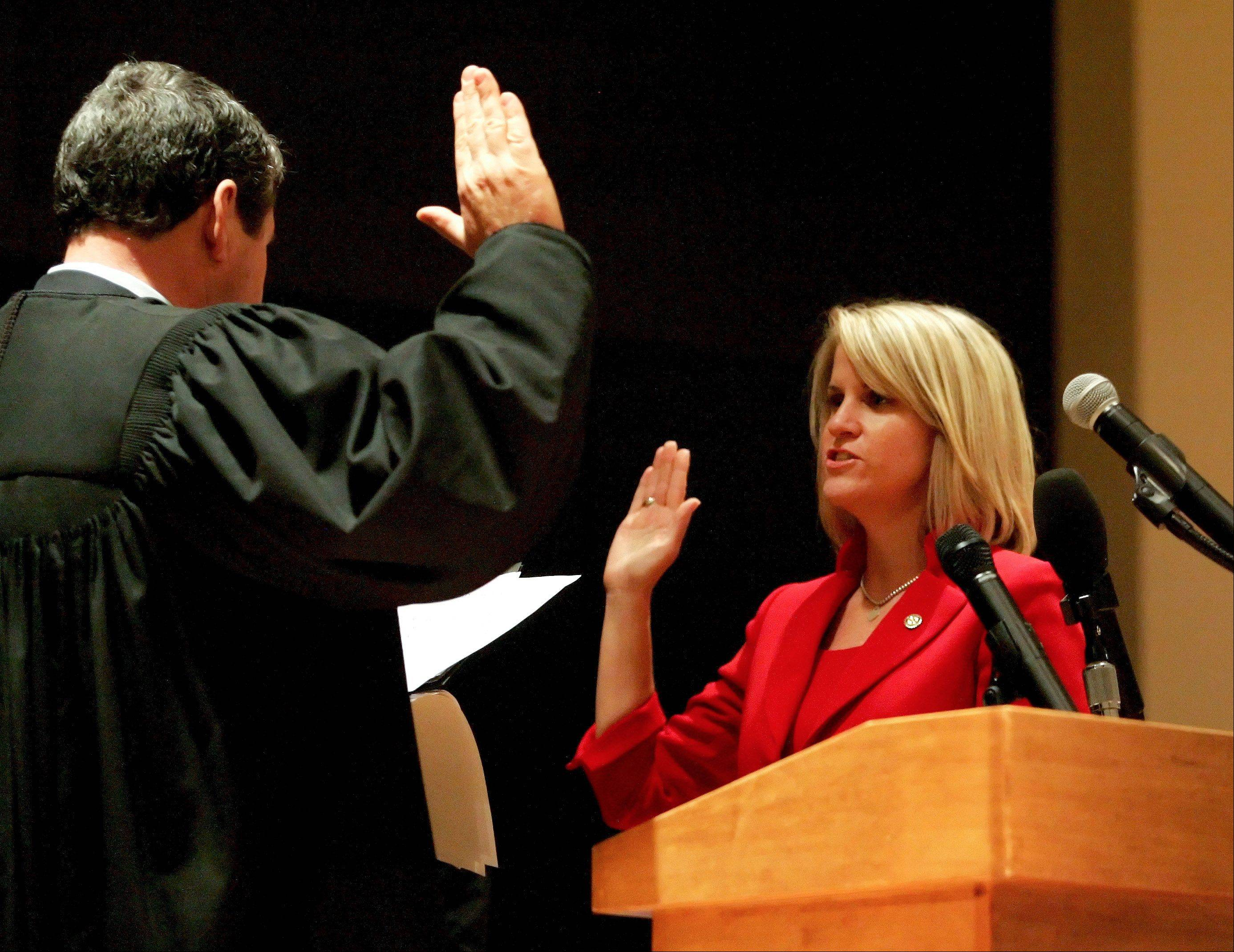 Tonia Khouri gets sworn in as a District 5 board member by Judge John Elsner during the 2012 Inauguration of DuPage County elected officials at the Jack T. Knuepfer Administration building in Wheaton on Monday.