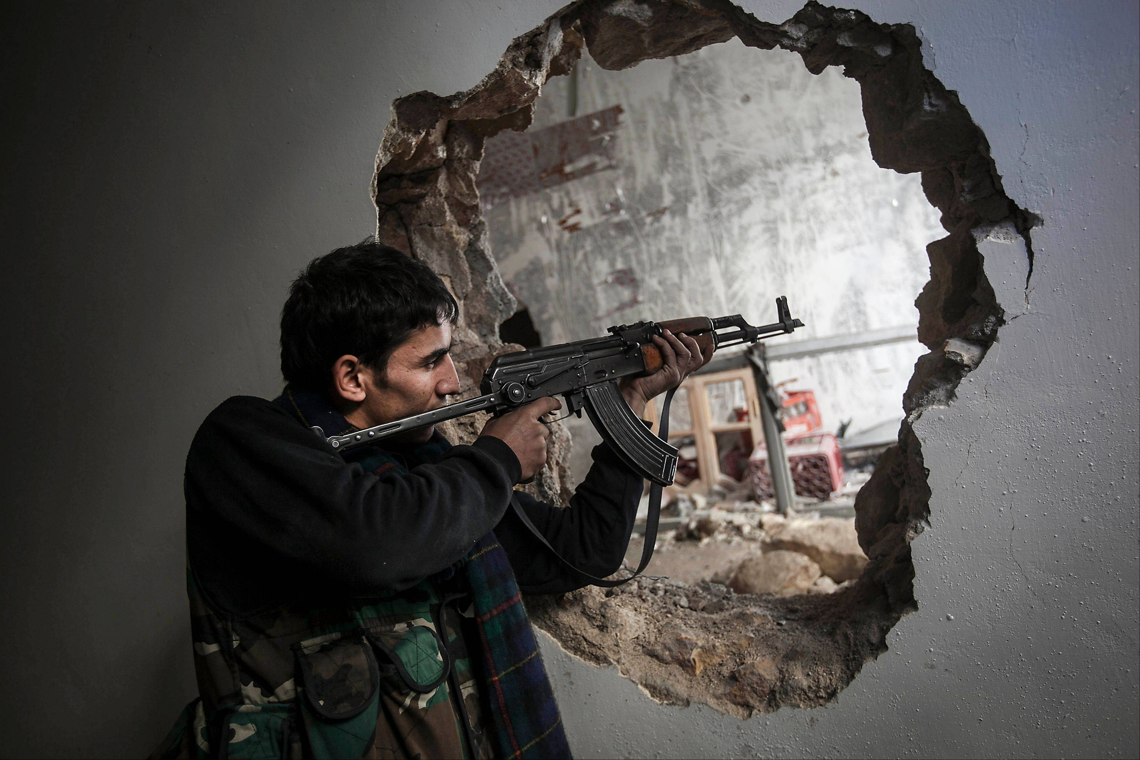 A Free Syrian Army fighter fires his weapon during clashes with government forces in Aleppo on Sunday.