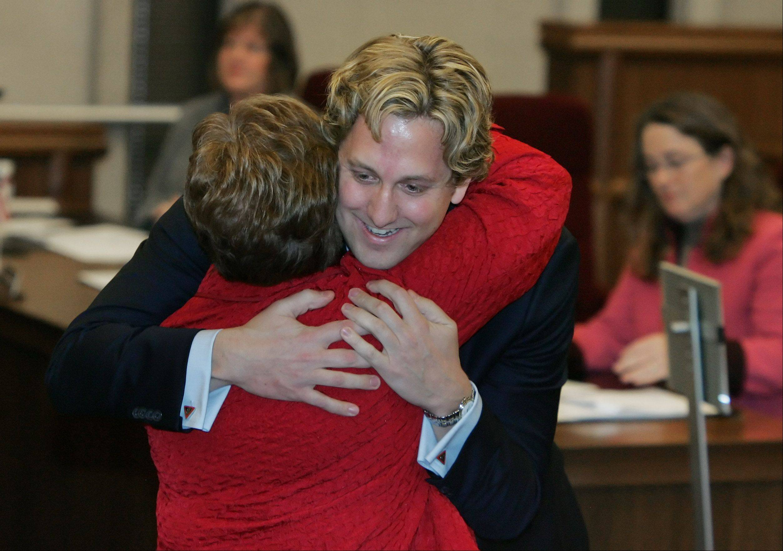 Aaron Lawlor is hugged by Carol Calabresa after he was named Lake County Board chairman on Monday. Calabresa was named vice chairman.
