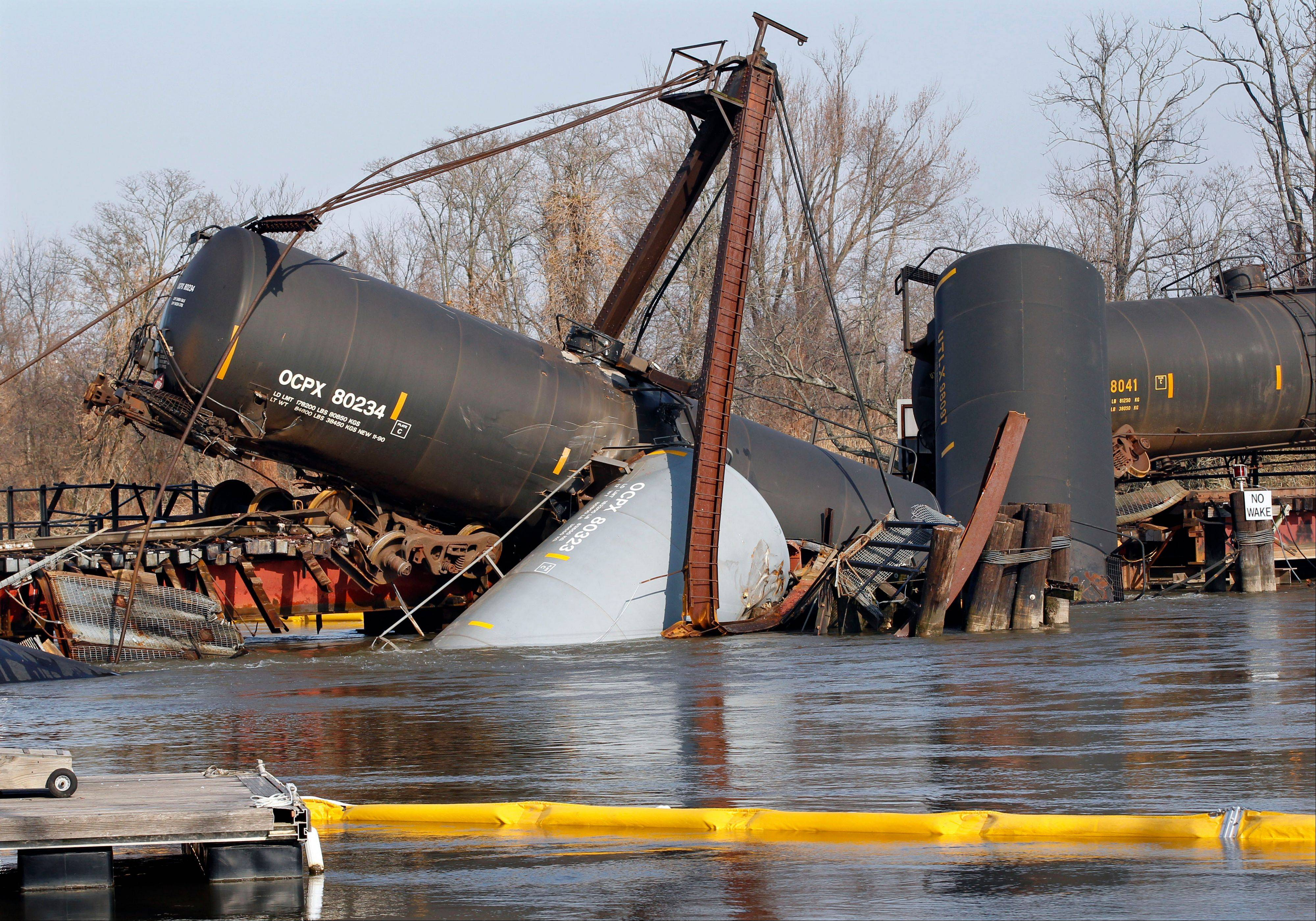 A containment boom floats in Mantua Creek Saturday near freight train tank cars that derailed Friday in Paulsboro, N.J. Residents in an area of about 12 blocks near the derailment remain out of their homes as officials continued their efforts to clear a hazardous gas that spewed from a ruptured freight train car.