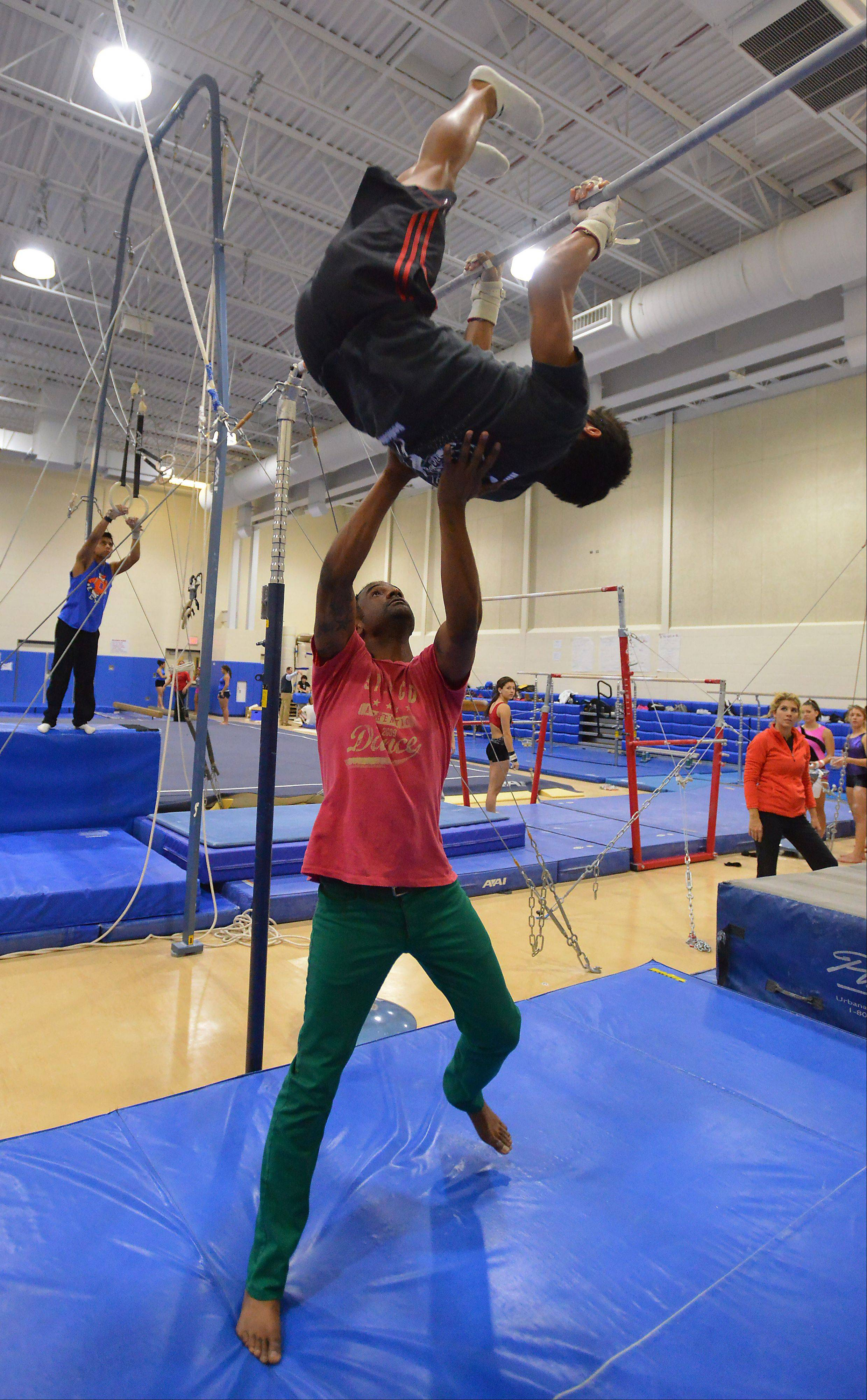 As coach, Brown spots gymnast Andres Cueva during practice.