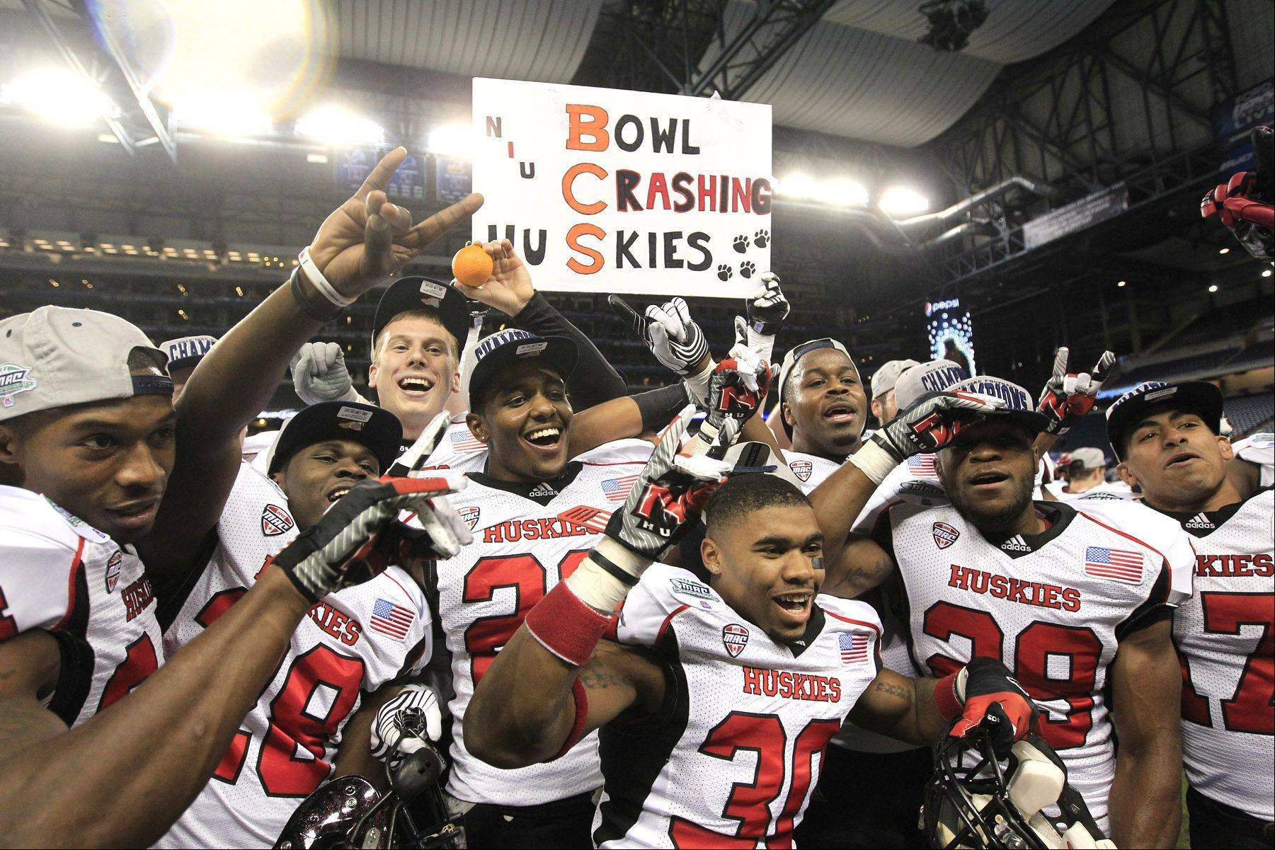 The Northern Illinois team poses for photographers after defeating Kent State 44-37 in double overtime in the Mid-American Conference championship in an NCAA college football game at Ford Field, Friday. After a wild weekend of events, NIU