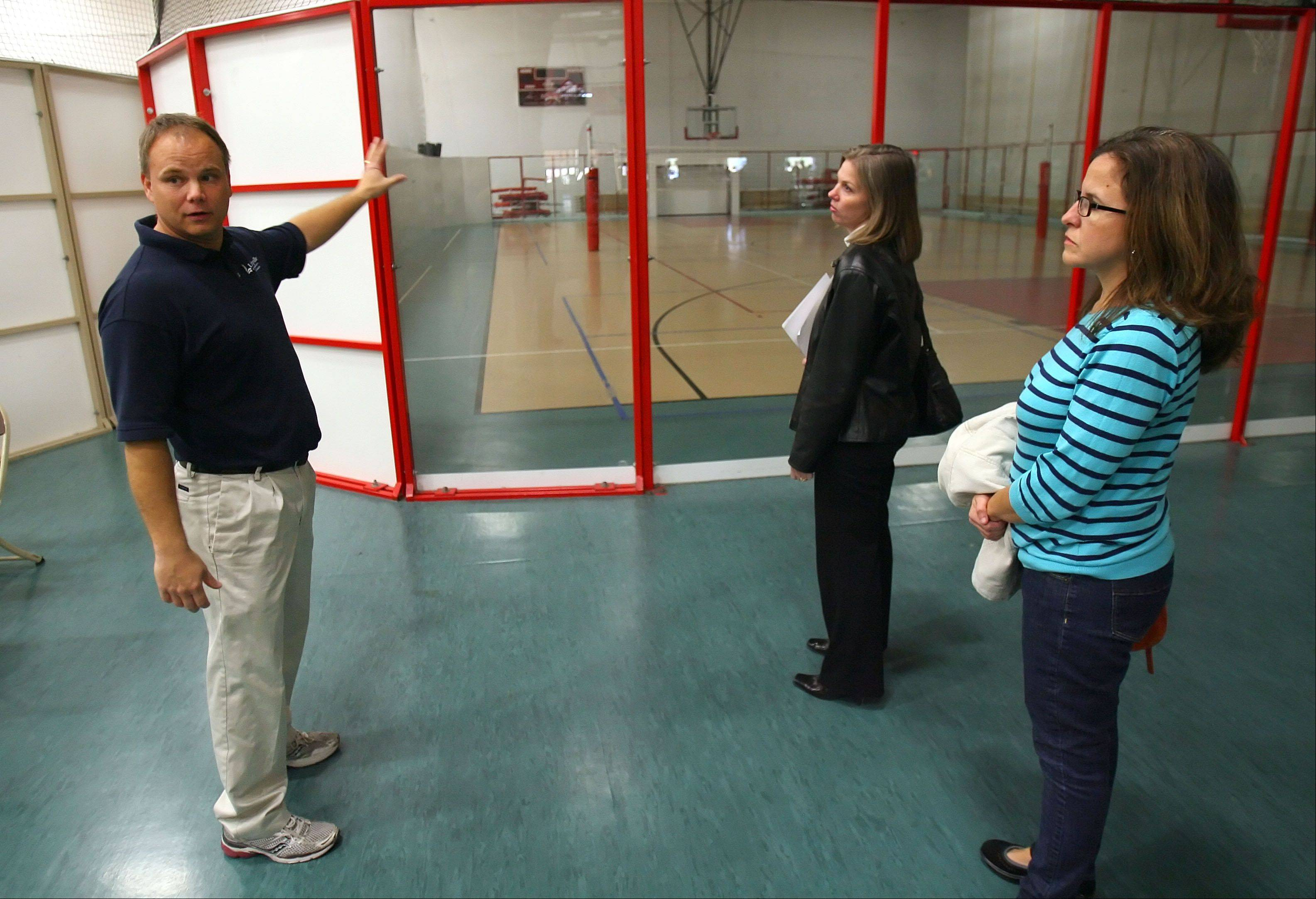Randy Splitt, facility manager for the Libertyville Sports Complex, talks to Dara Dietmeyer and Colleen Scopacasa, right, about the set up for an overnight New Year's Eve celebration for fifth- to eighth-graders. The event is a fundraiser for a youth baseball team.