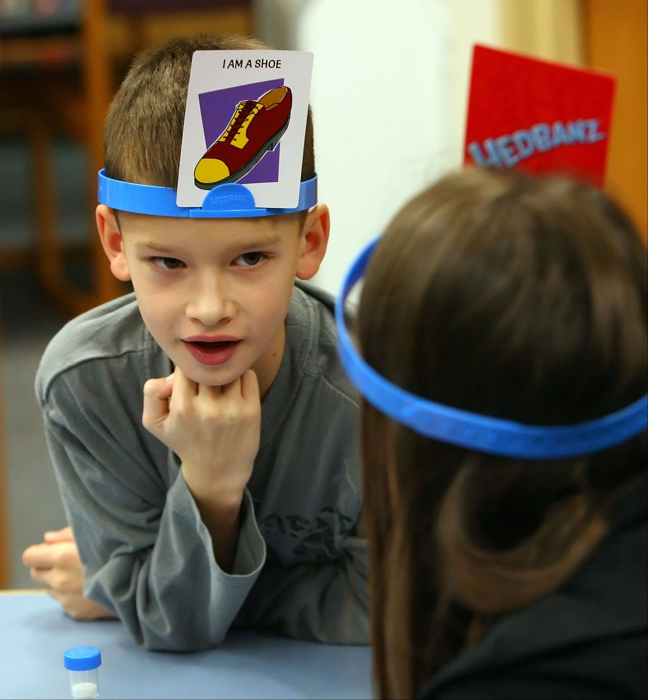 Second grader Joe Butler, left, plays a game called Hedbanz with teacher Danya Greenberg during an after school program called Games Galore at Rockland School in Libertyville Monday.