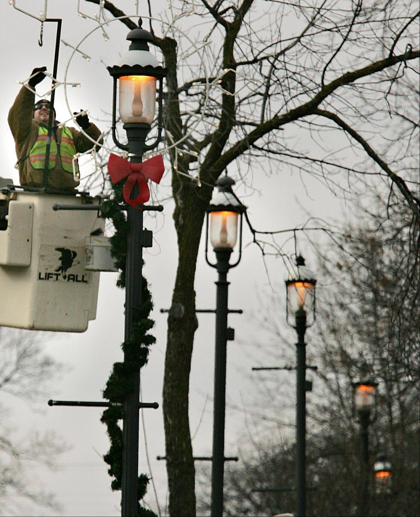 West Dundee Public Works employee Anthony Faflik of Rolling Meadows helps install holiday decorations along Rt. 72 in downtown West Dundee Monday. In order to hit all the lamp posts along that stretch of road, the crew will be working through Tuesday to get all of the decorations installed.