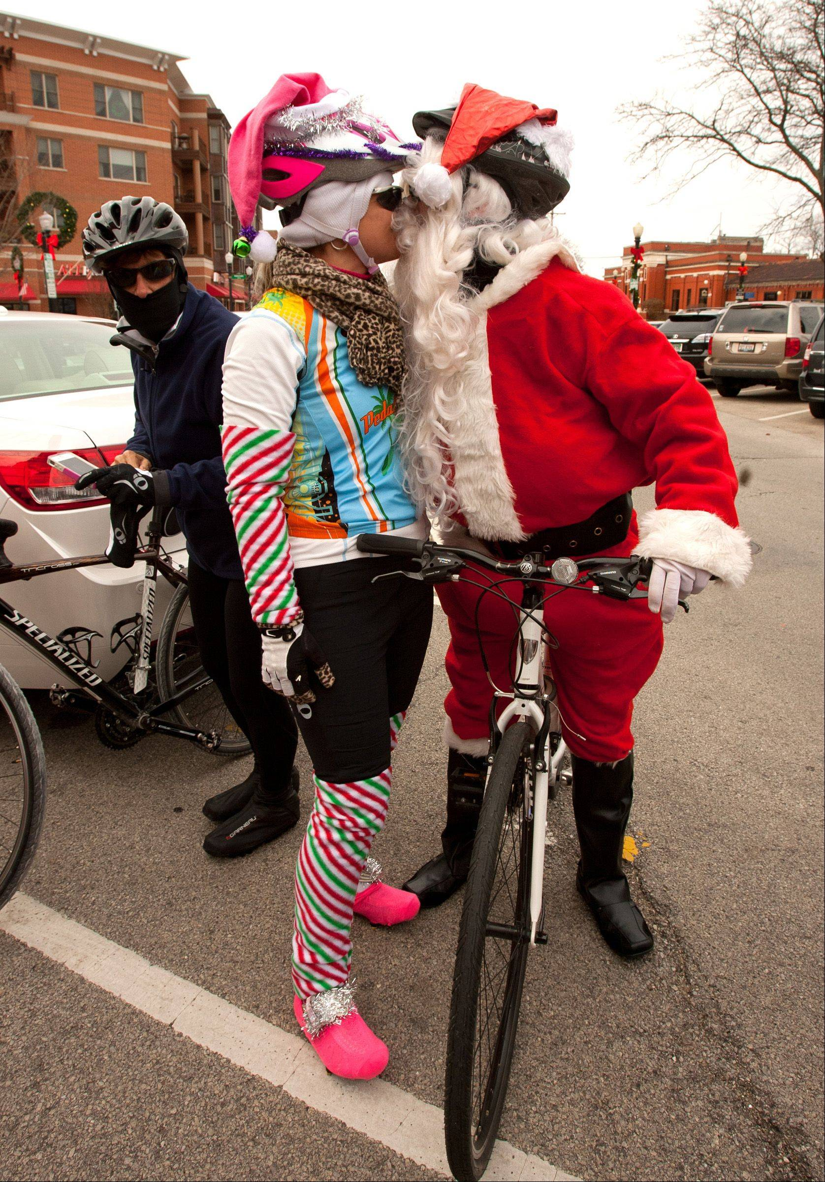 Vita Zadura of Chicago embraces her fiancee Mark Deles, of Mt. Prospect. They, along with other members of the Pedal Heads bicycle club, rode from downtown Downers Grove to Good Samaritan Hospital wearing Santa suits to deliver gifts to hospitalized children.