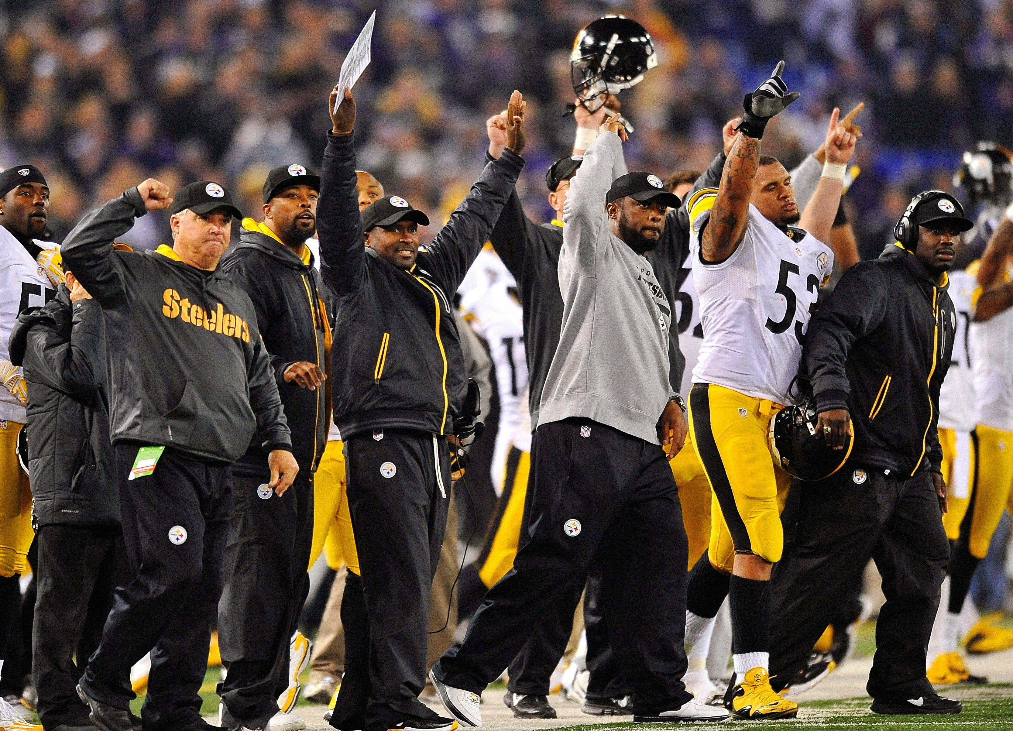 Pittsburgh Steelers head coach Mike Tomlin, center, joins the rest of the bench Sunday in celebrating the winning field goal dagainst the Baltimore Ravens in Baltimore.