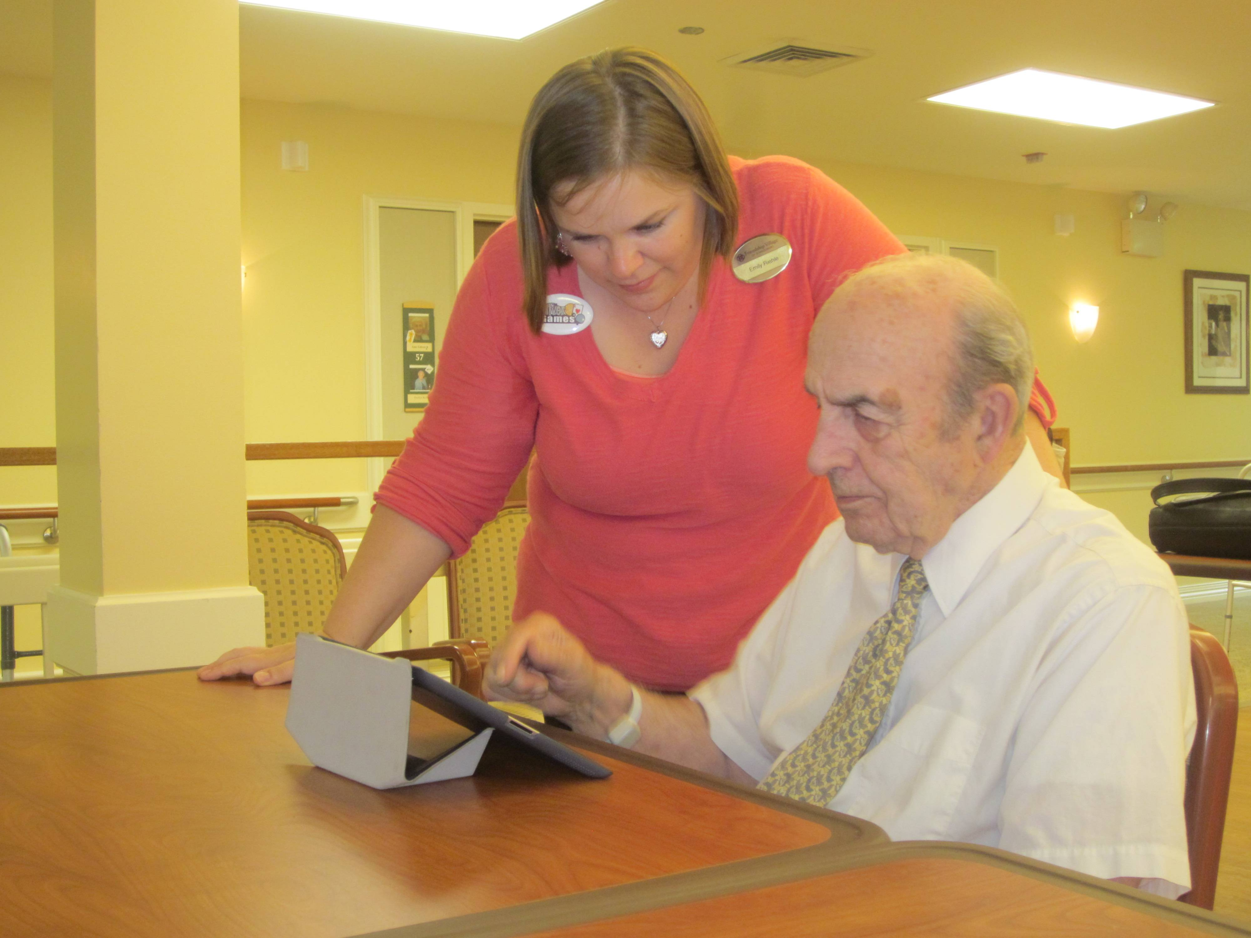 Emily Riehle, activities manager for Briarwood Healthcare working with a resident of the community on an iPad.