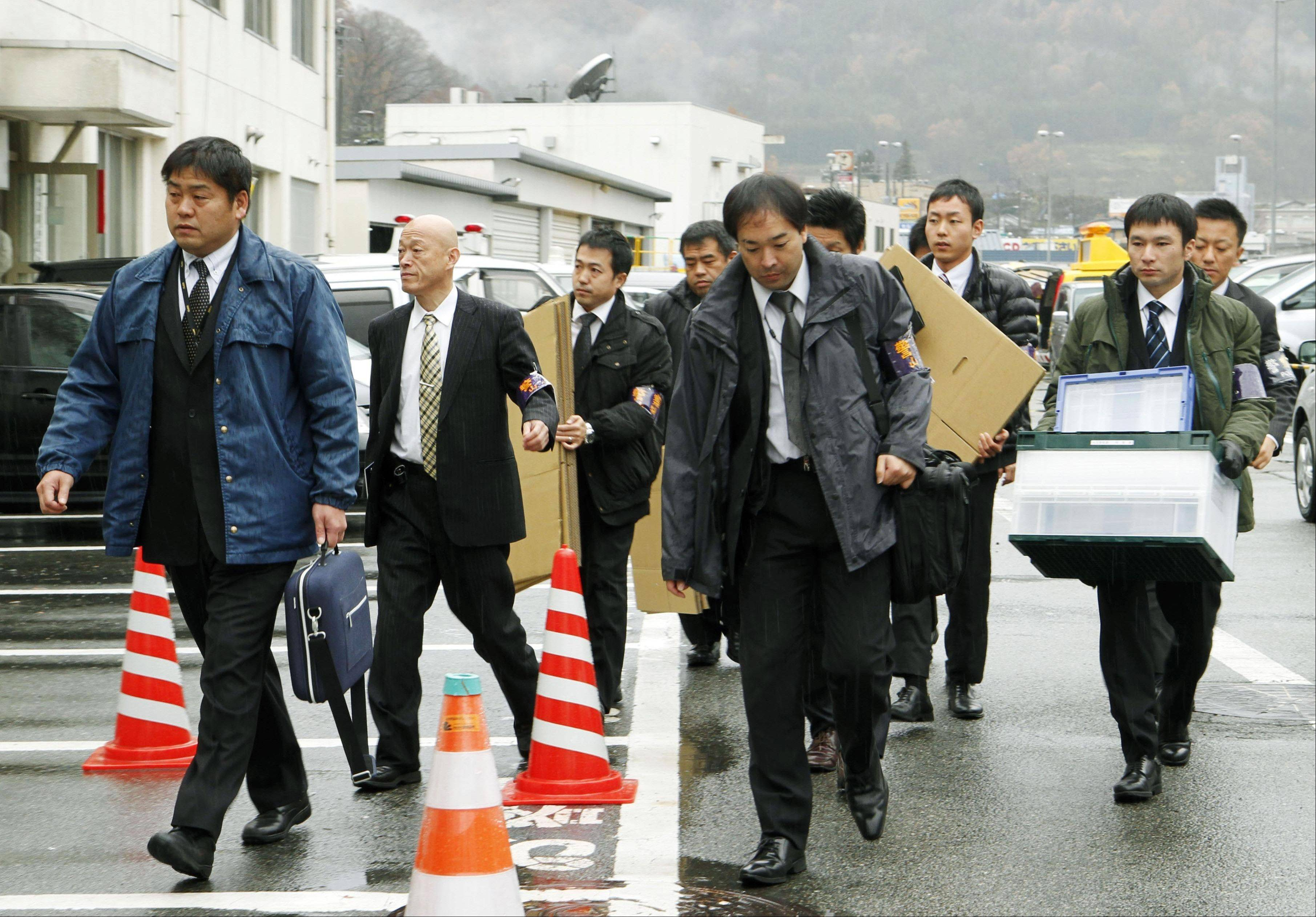 Yamanashi Prefectural police investigators arrive Tuesday at Central Japan Expressway Co. to search the office in Otsuki, near Tokyo. Police were searching the offices Tuesday of the company operating an expressway tunnel where hundreds of concrete ceiling slabs collapsed onto moving vehicles below, killing nine people.