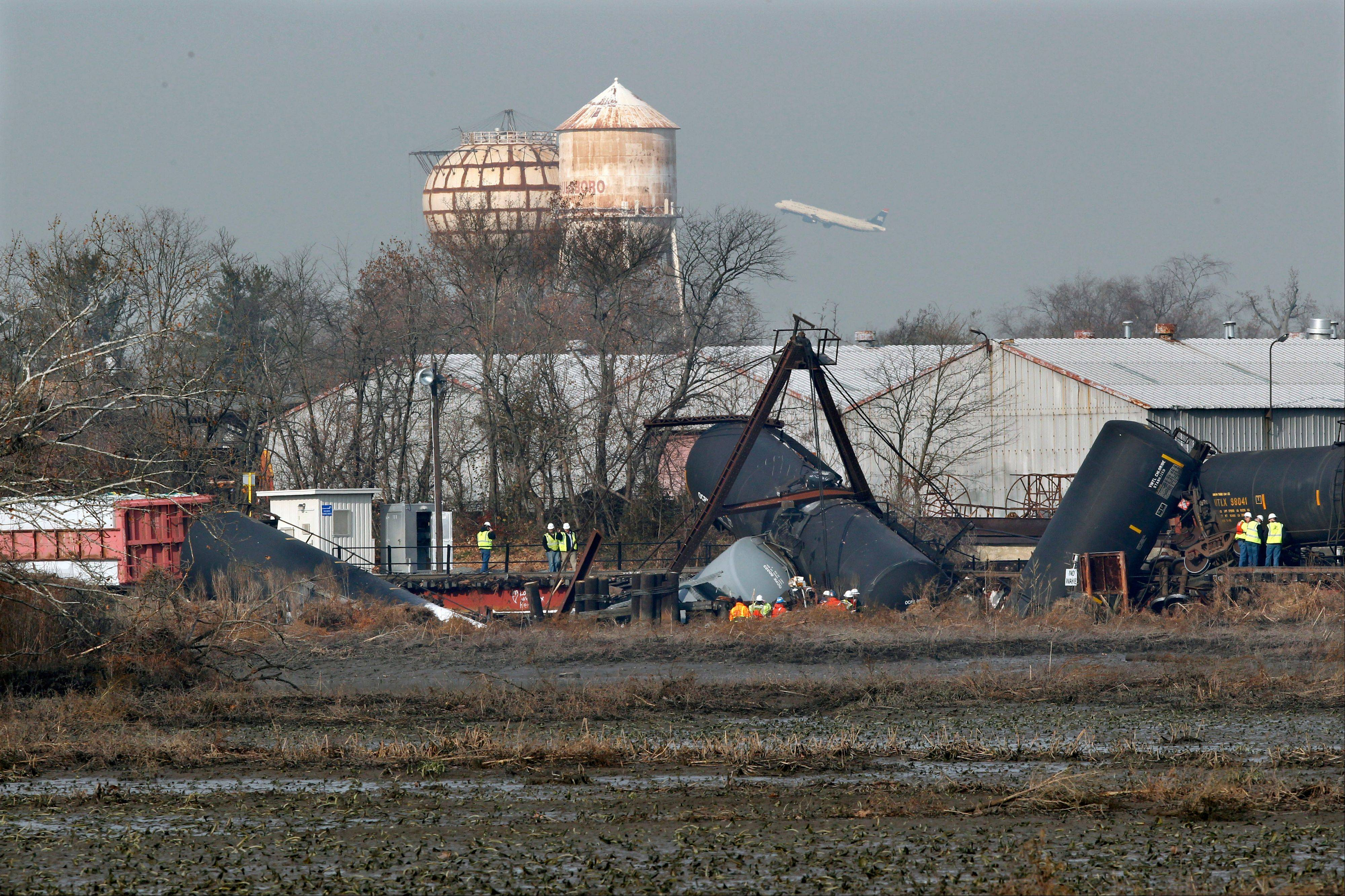 Officials work the scene of derailed freight train tank cars on Friday in Paulsboro, N.J. Residents of Paulsboro were ordered to stay inside and schools were closed Monday after unsafe levels of the chemical vinyl chloride were found in the air near where the train derailed last week.