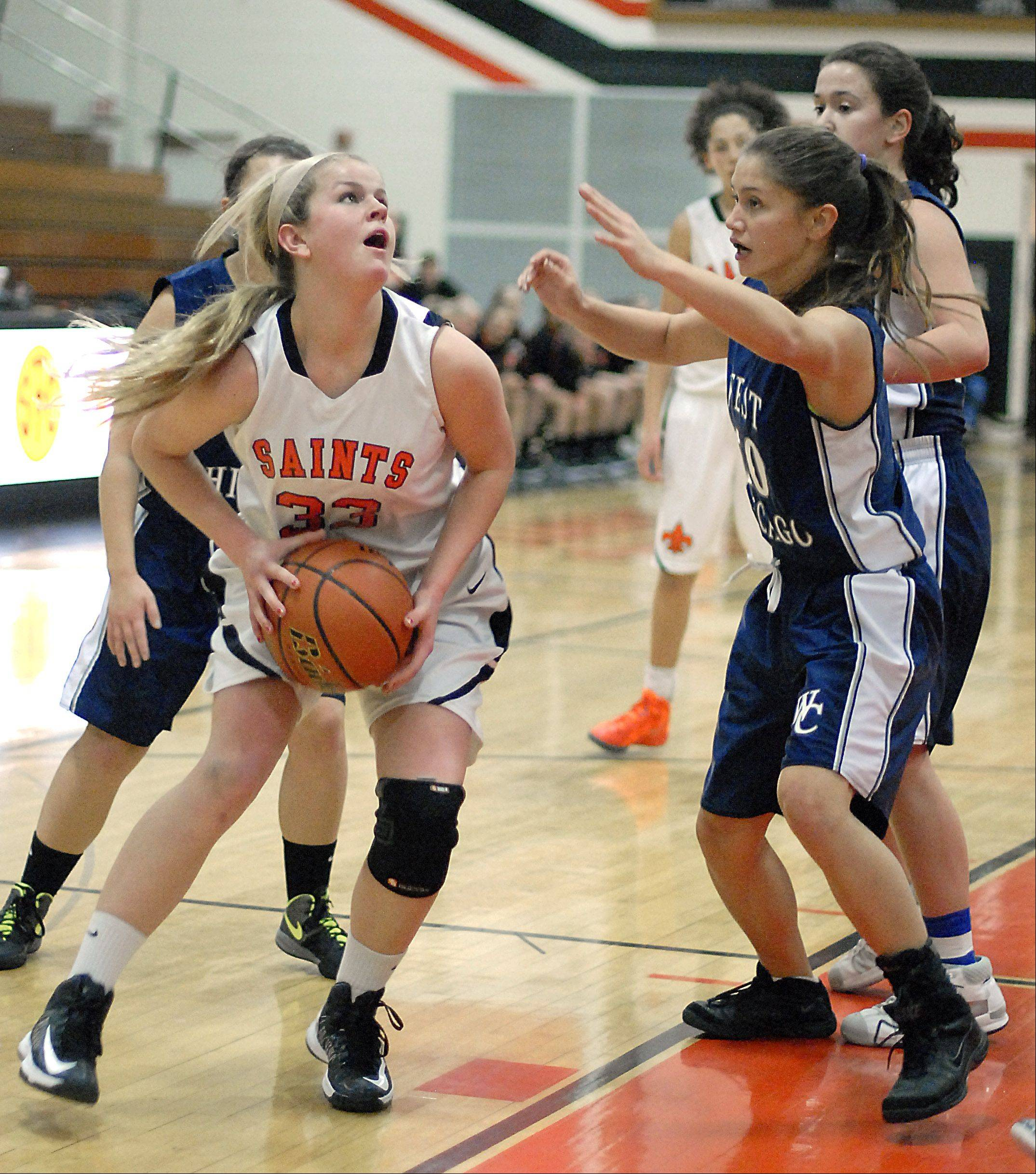 St. Charles East�s Hannah Nowling looks to shoot over a block by West Chicago�s Amanda Gosbeth in the second quarter on Tuesday, December 4.
